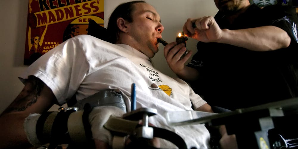 DENVER, CO, JUNE, 6, 2005 - Micah Moffett, a quadriplegic confined to a wheelchair since a motorcycle accident in 1991, needs assistance from his licensed marijuana caregiver, Jay Buzzalini to help administer his medical dose. Buzzalin