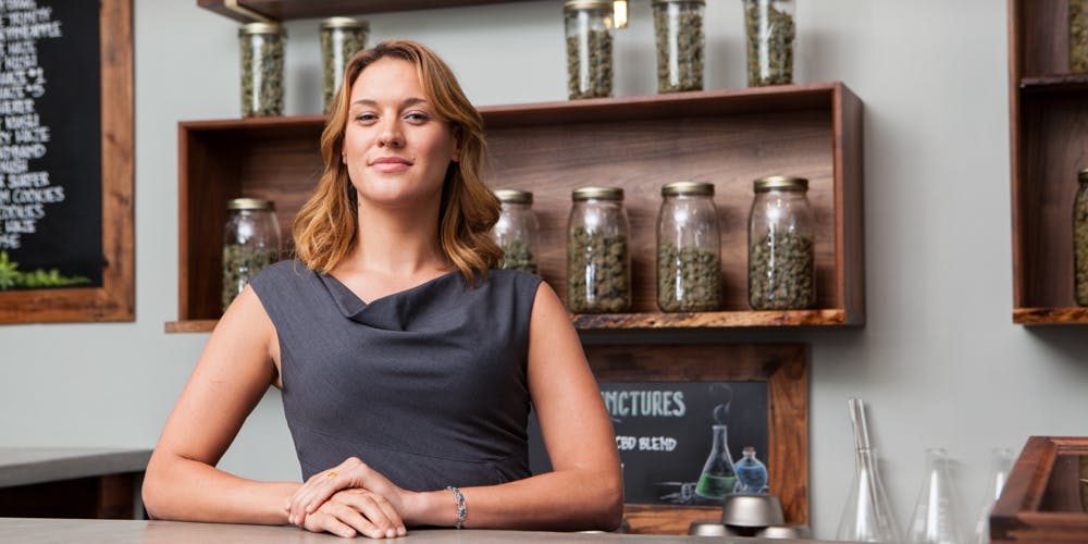 a female owner of a marijuana dispensary in Portland Oregon poses with cannabis product