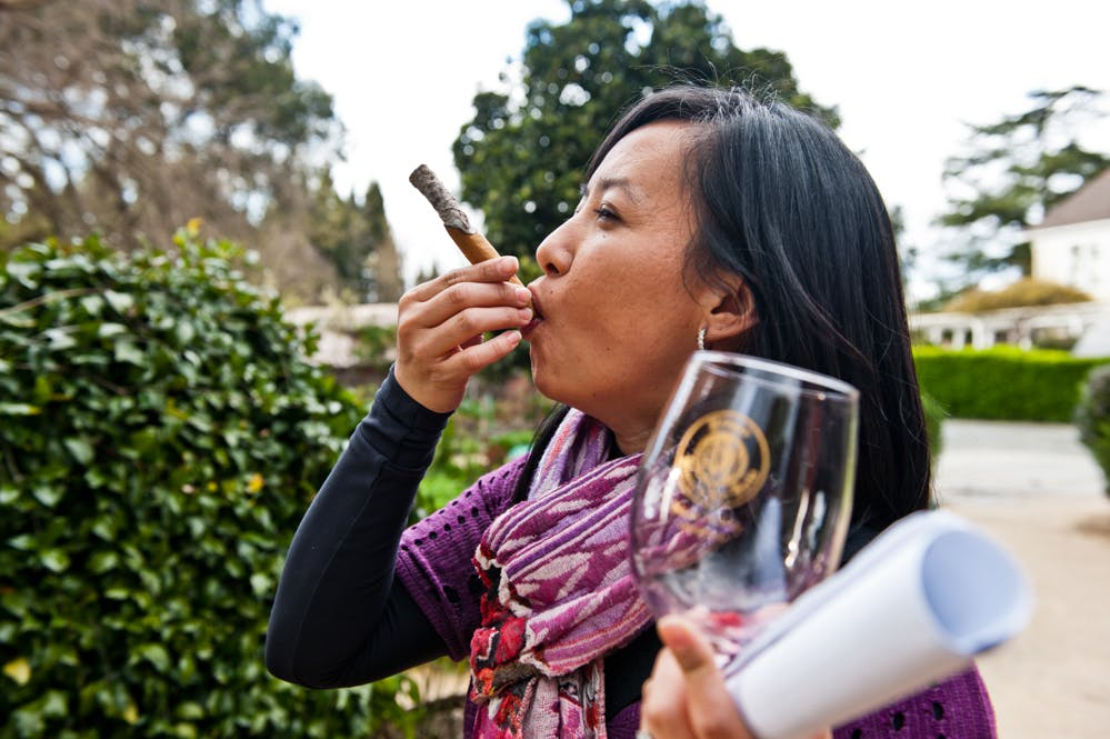 Woman smokes a blunt with a glass of wine in hand