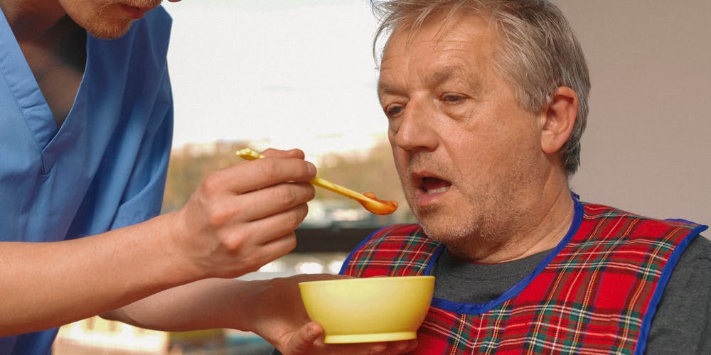 enior man getting fed by carer in care home