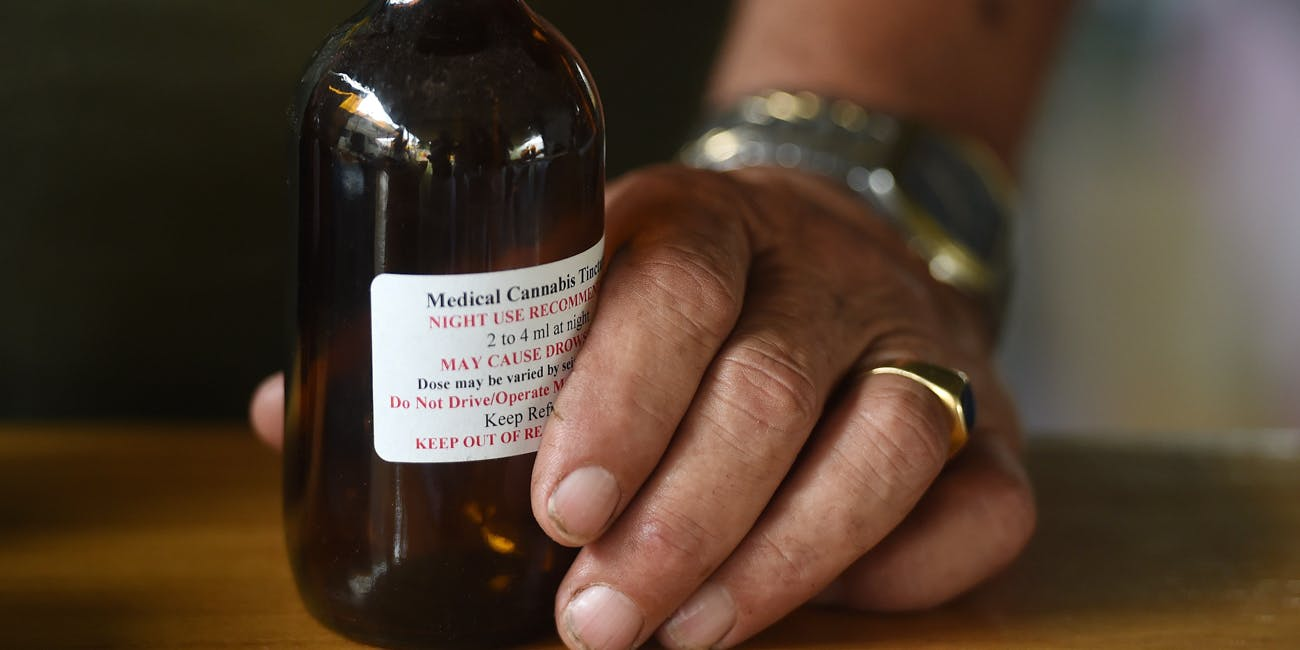 Hand holding a bottle of medical cannabis oil
