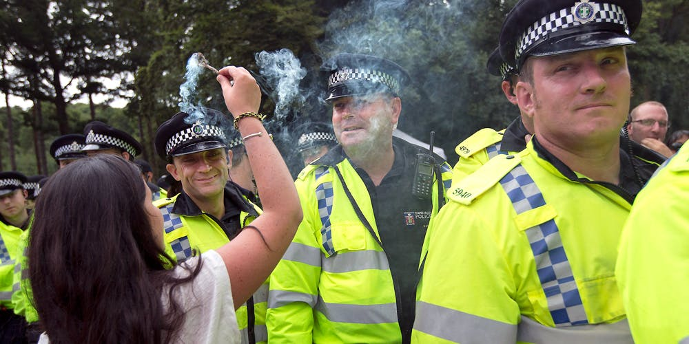 Woman puts incense in front of UK police face