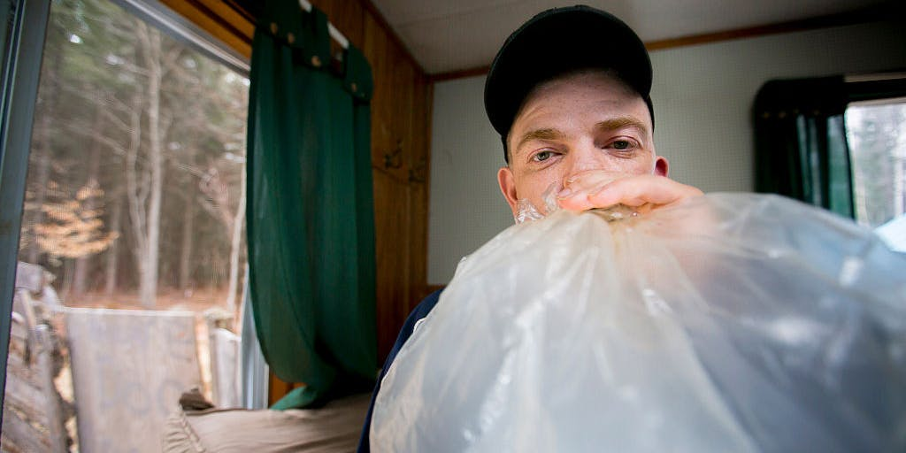 Man smoking medical marijuana vapor from a plastic bag in his home.