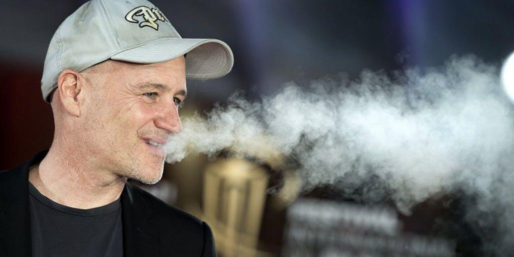 Older man blowing out smoke
