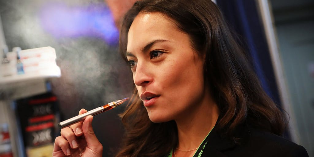 Women vapes a CBD oil made from hemp