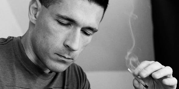Black and white portrait of Russ Hudson smoking a joint