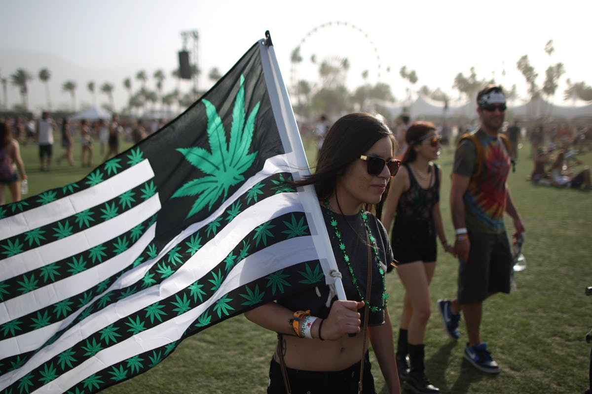 A woman carries a flag bearing marijuana symbol