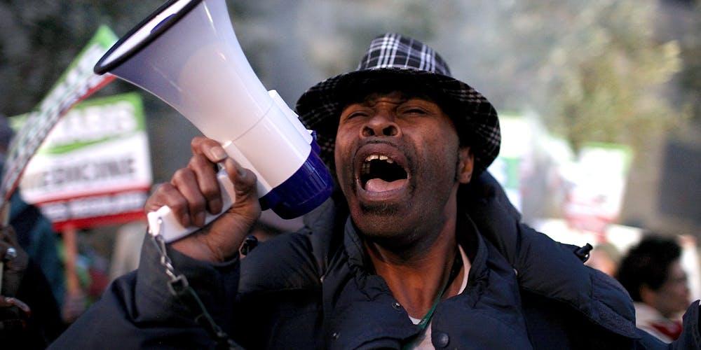 Man of colour uses a bullhorn