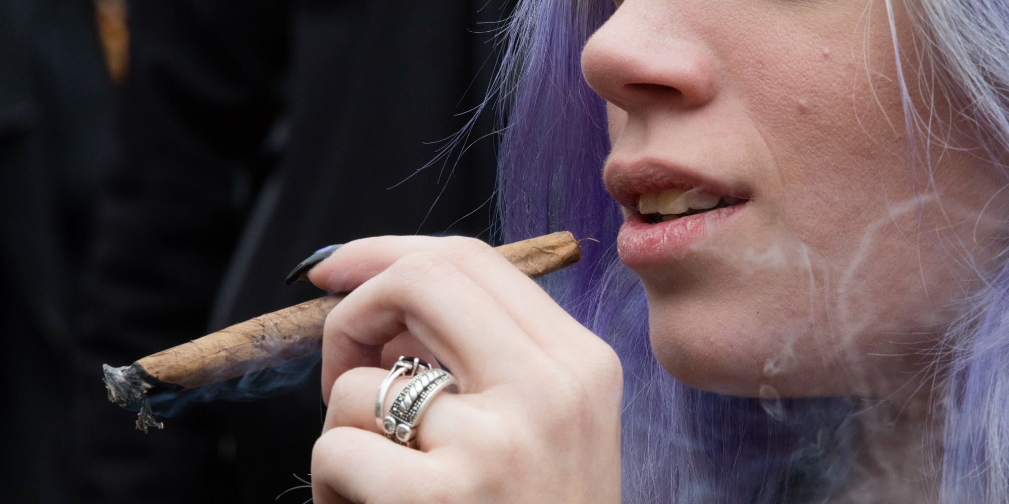 woman smokes cannabis during the annual NYC Cannabis Parade. Turns out women smoke more than men