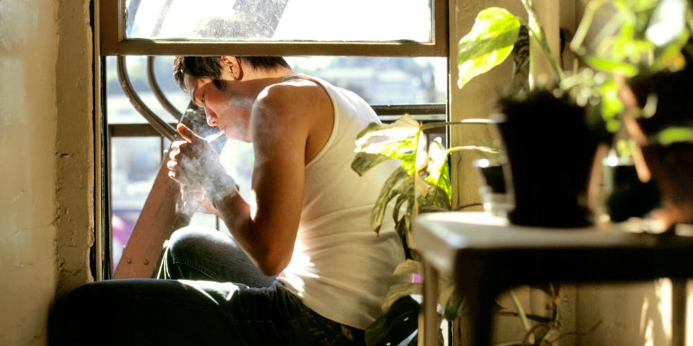 Young asian man smoking next to a window