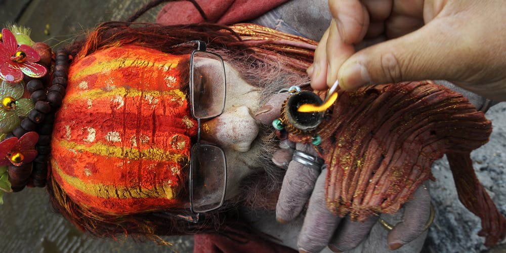 A Hindu Sadhu (holy man) smokes marijuana from a clay pipe as a holy offering for Lord Shiva