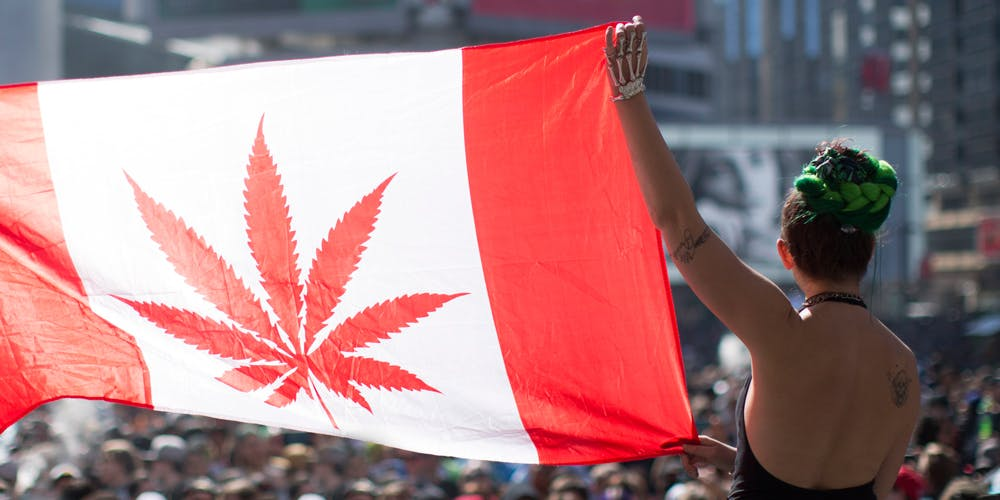 Woman holding up Cannabis Canada Flag