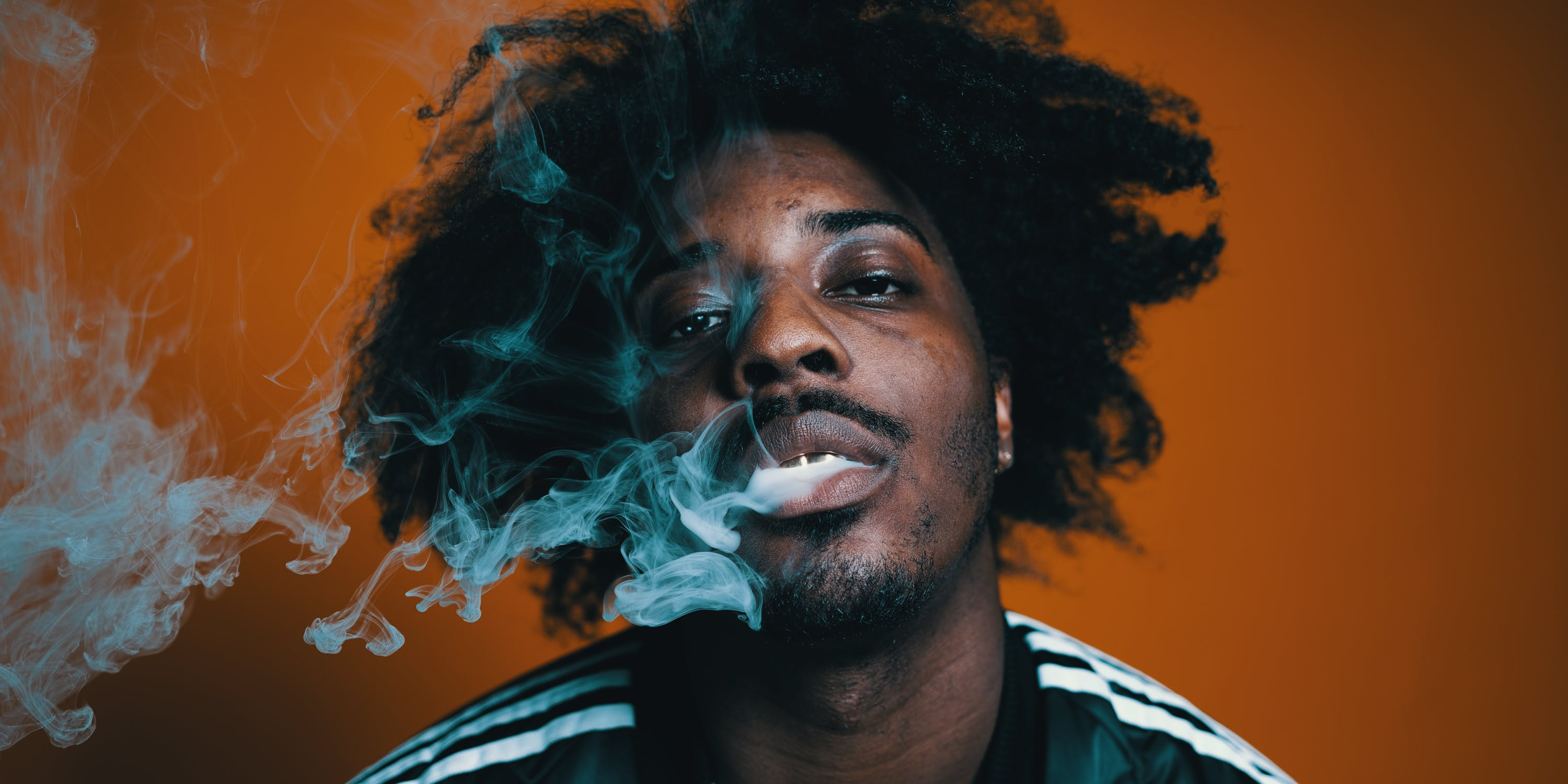 Sean Leon blows out a milky cloud of marijuana smoke