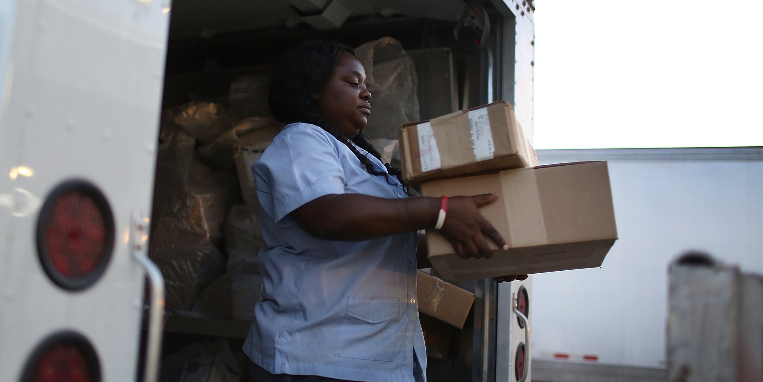 Women carrying packages off of a truck mail weed