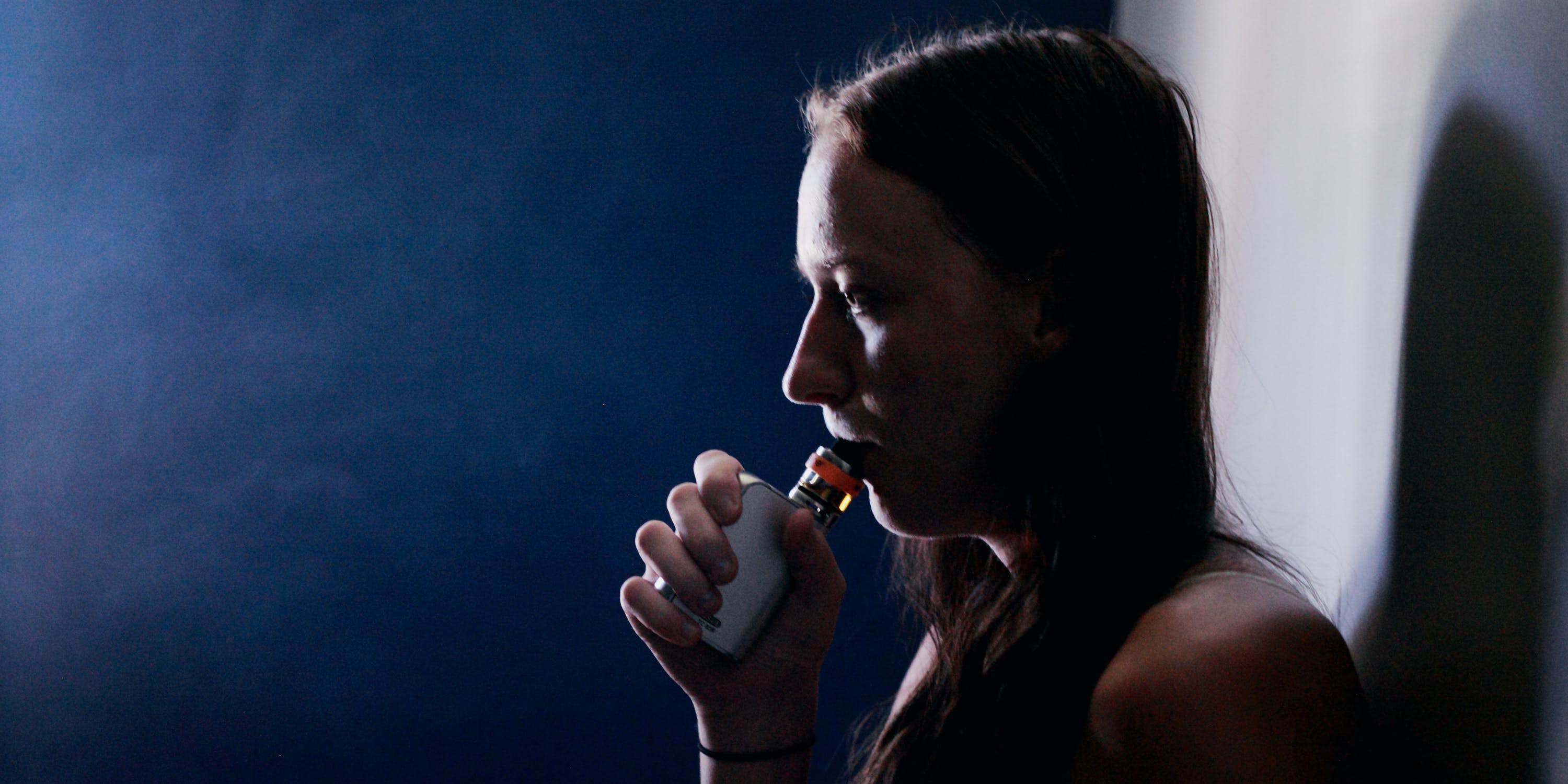 Side View Of Young Woman Smoking vape By Wall At Night