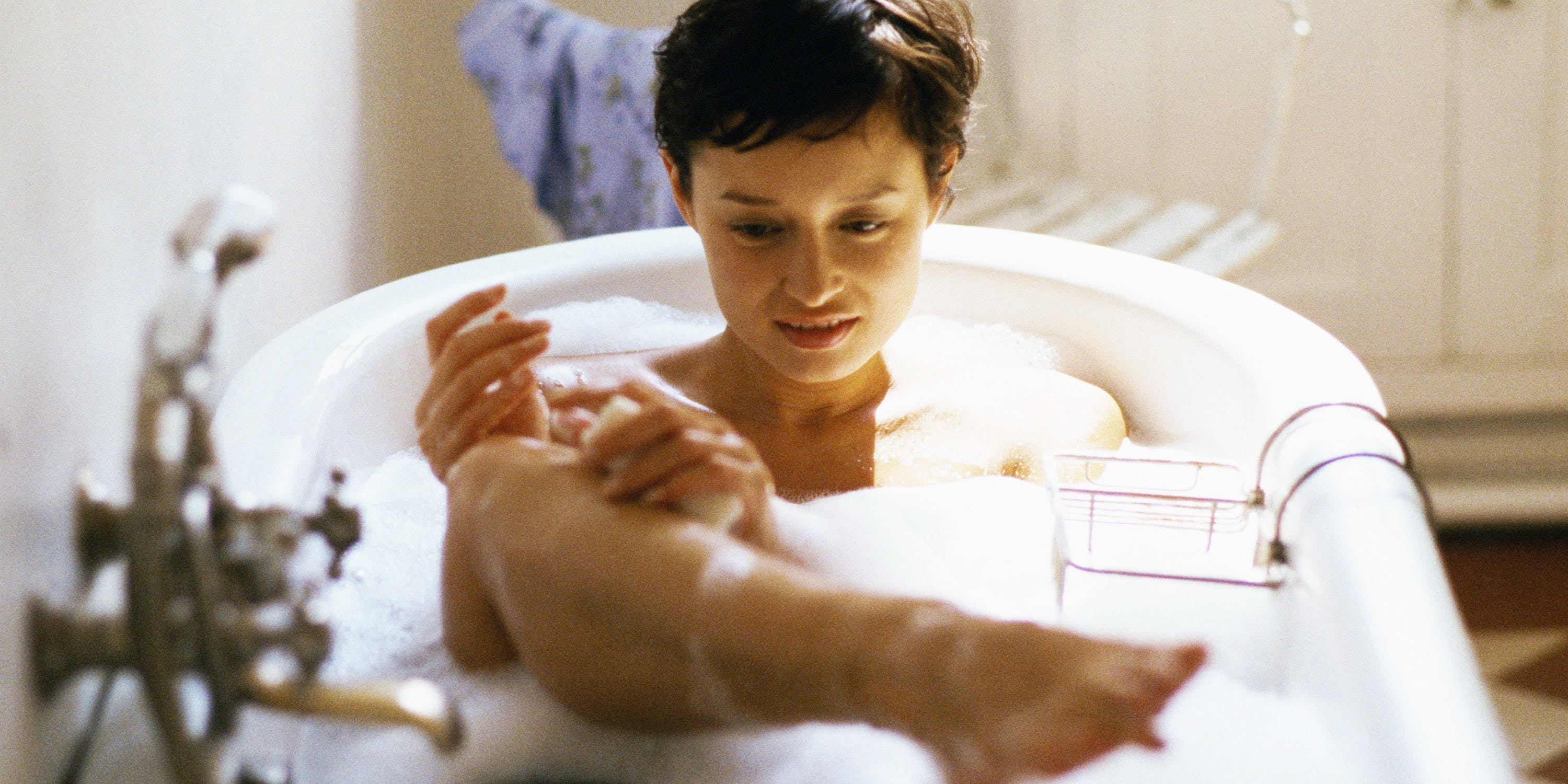 Woman taking bath, holding leg out of water
