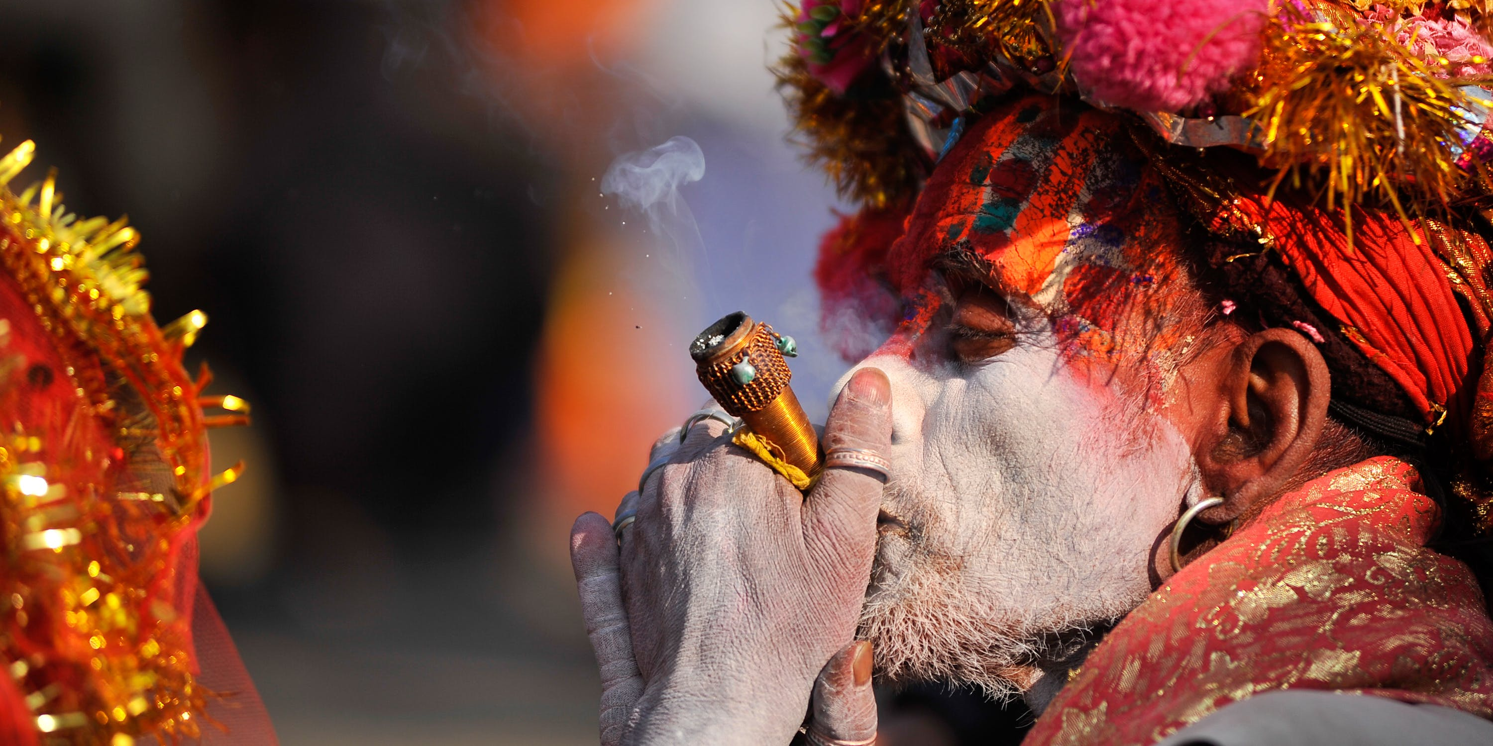 A colorful Hindu Sadhu or Holy Man smokes marijuana at the