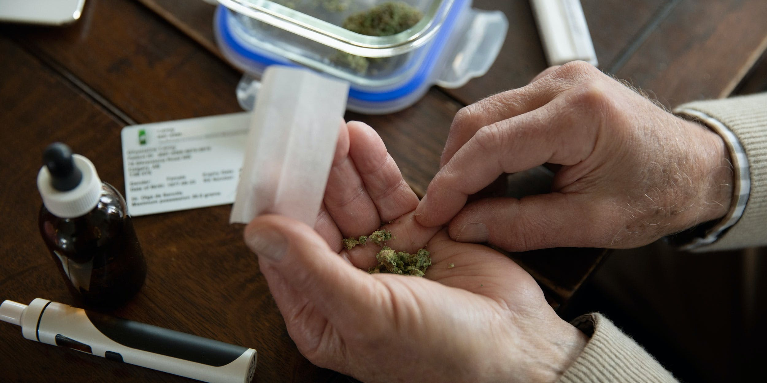 Medical Marijuana in an old mans hands next to cbd oil and a vaporizer