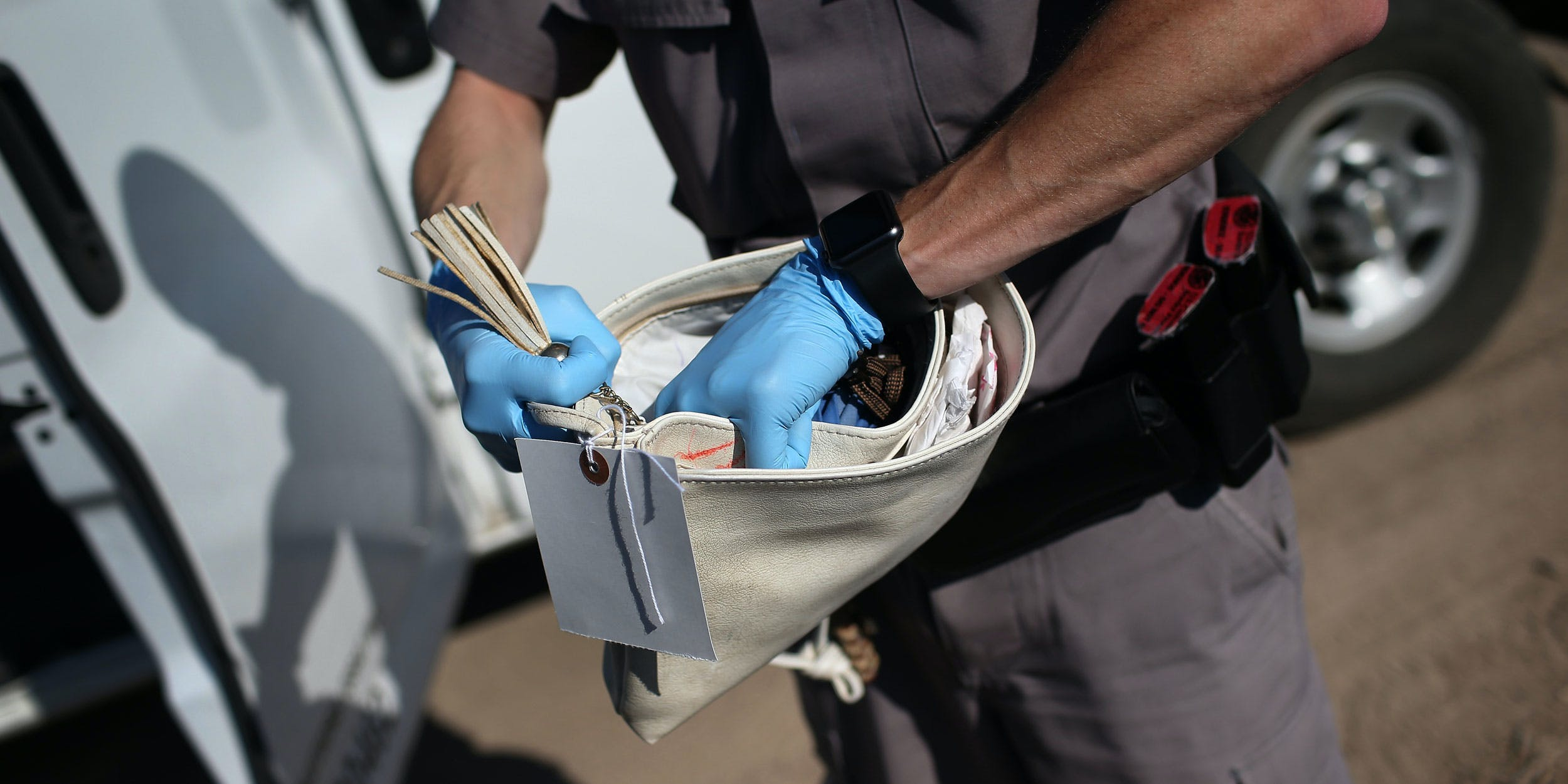 RIO GRANDE CITY, TX - DECEMBER 07: A Border security agent searches the purse of an undocumented immigrant from El Salvador after she illegally crossed the U.S.-Mexico border and was caught by the U.S. Border Patrol on December 7, 2015 near Rio Grande City, Texas. Border Patrol agents continue to capture hundreds of thousands of undocumented immigrants each year trying to sneak into the United States, even as migrant families and unaccompanied minors from Central America cross and turn themselves in to seek asylum. (Photo by John Moore/Getty Images)