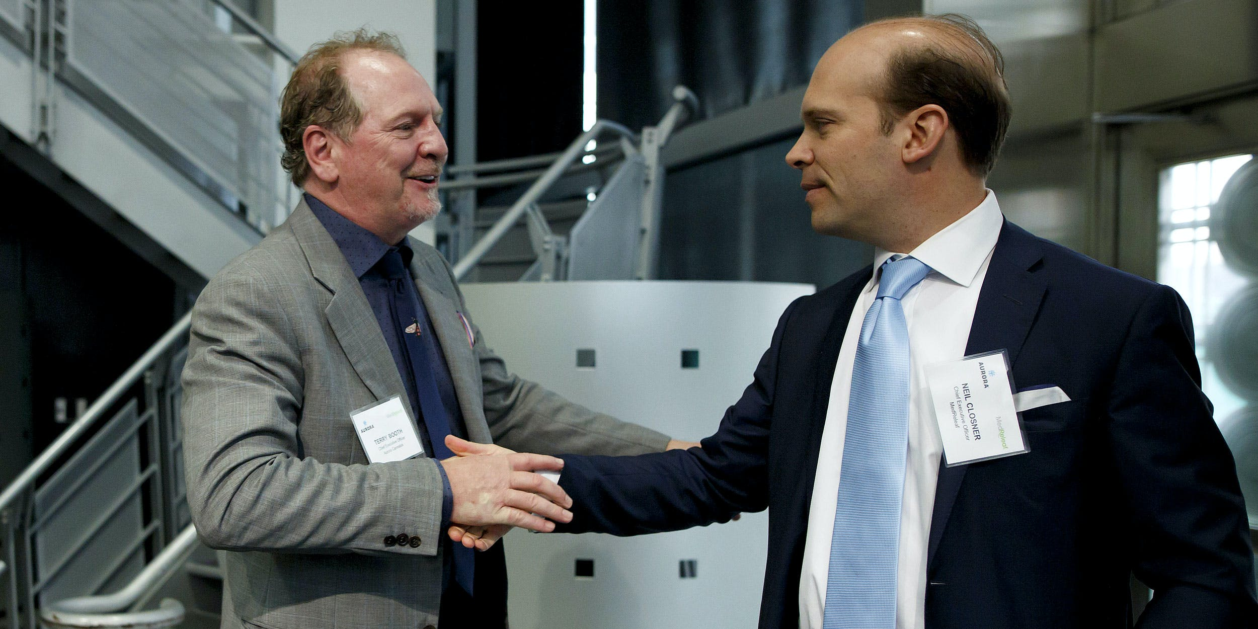 Terry Booth, chief executive officer of Aurora Cannabis Inc., left, shakes hands with Neil Closner, chief executive officer of MedReleaf Corp., during a news conference at the Toronto Stock Exchange