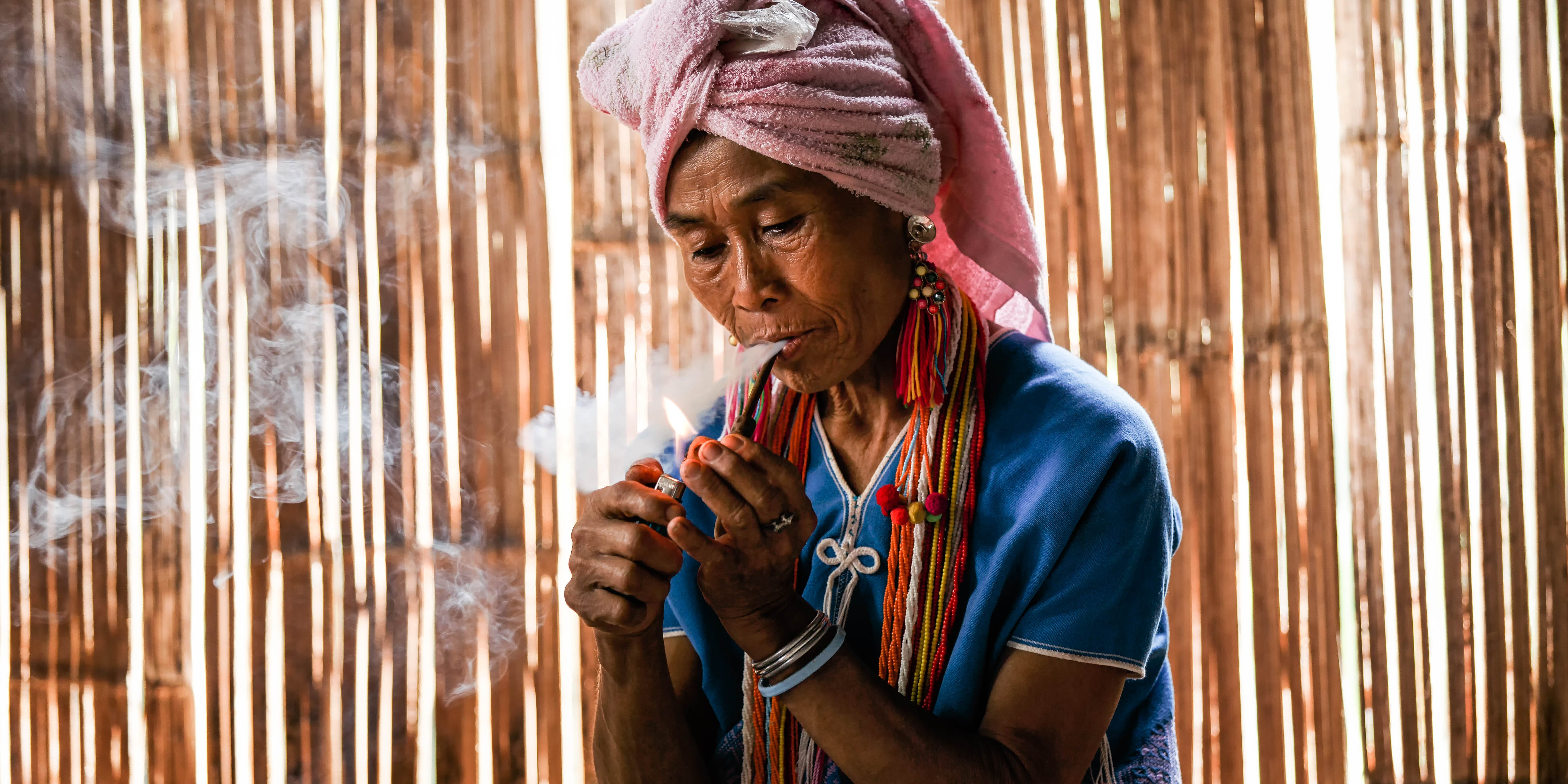A member of Thailand's karen hill tribe smokes from a tobacco pipe in the Chiang Mai Province. (Photo by Pakin Songmor via Getty images )