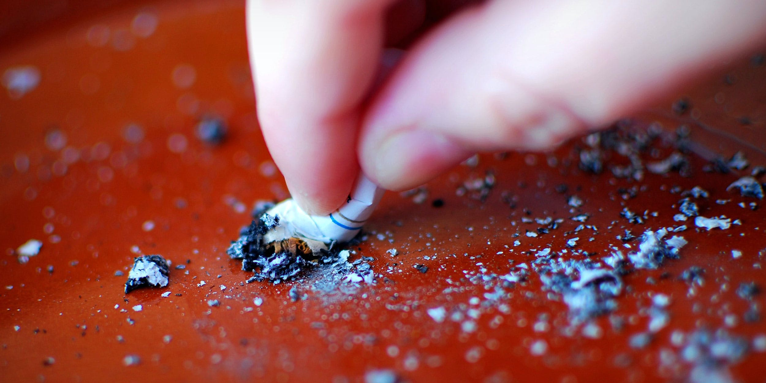 cigarette being put out on a red surface
