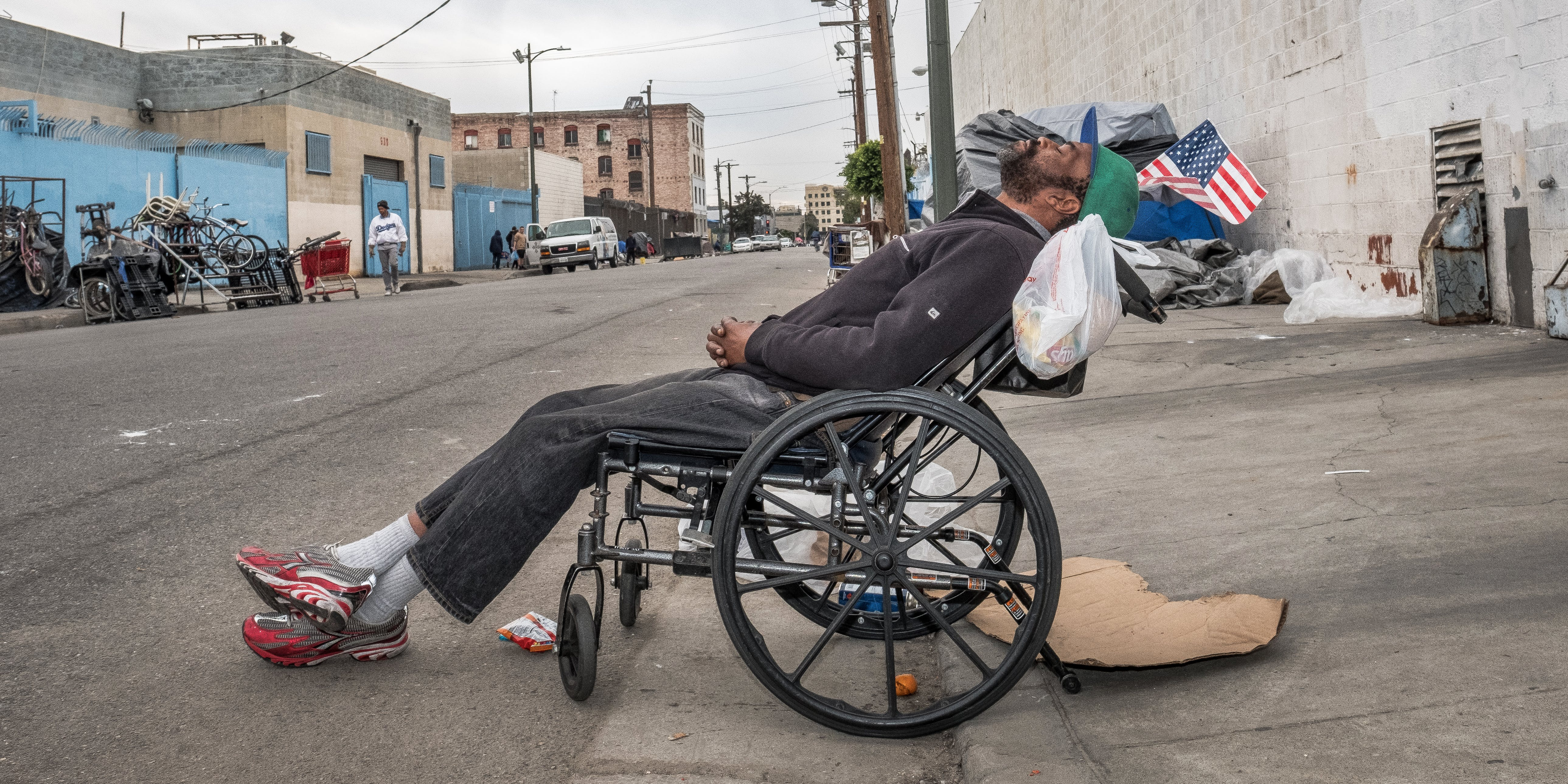 Man in wheelchairs sit on sidewalk, reclined, asleep.