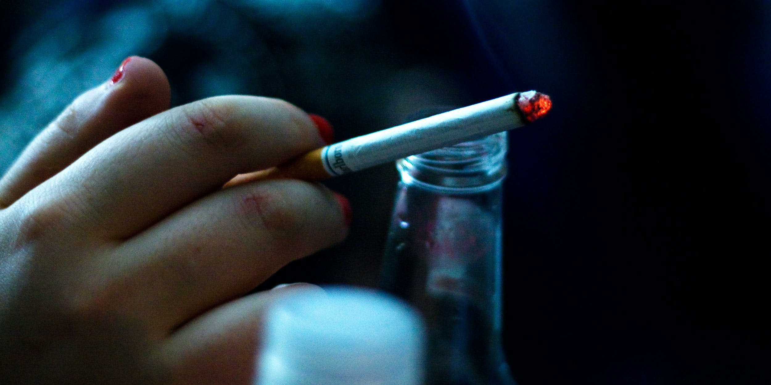 Beer bottle and a hand holding a cigarette. A new review of global substance use data has shown that alcohol and tobacco are far more harmful than cannabis.