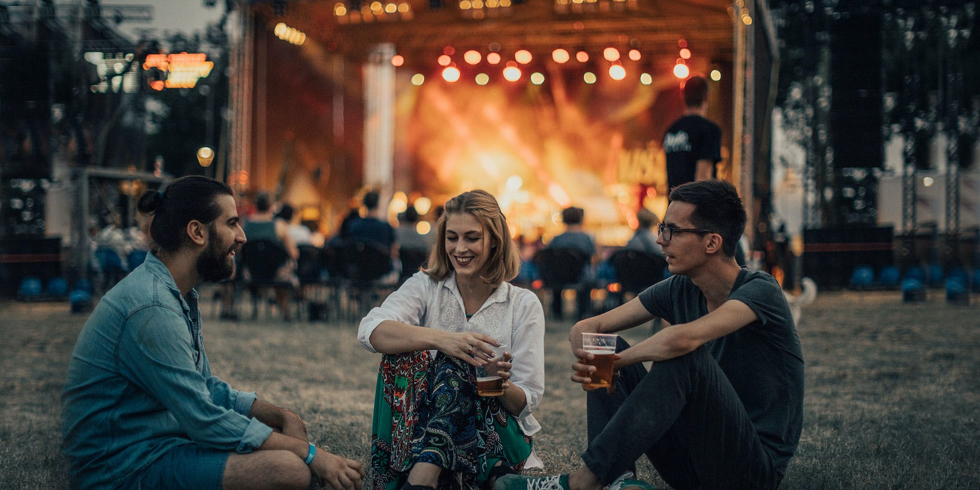 Three young adults sitting infront of a music concert talking about best vaporizer for concerts