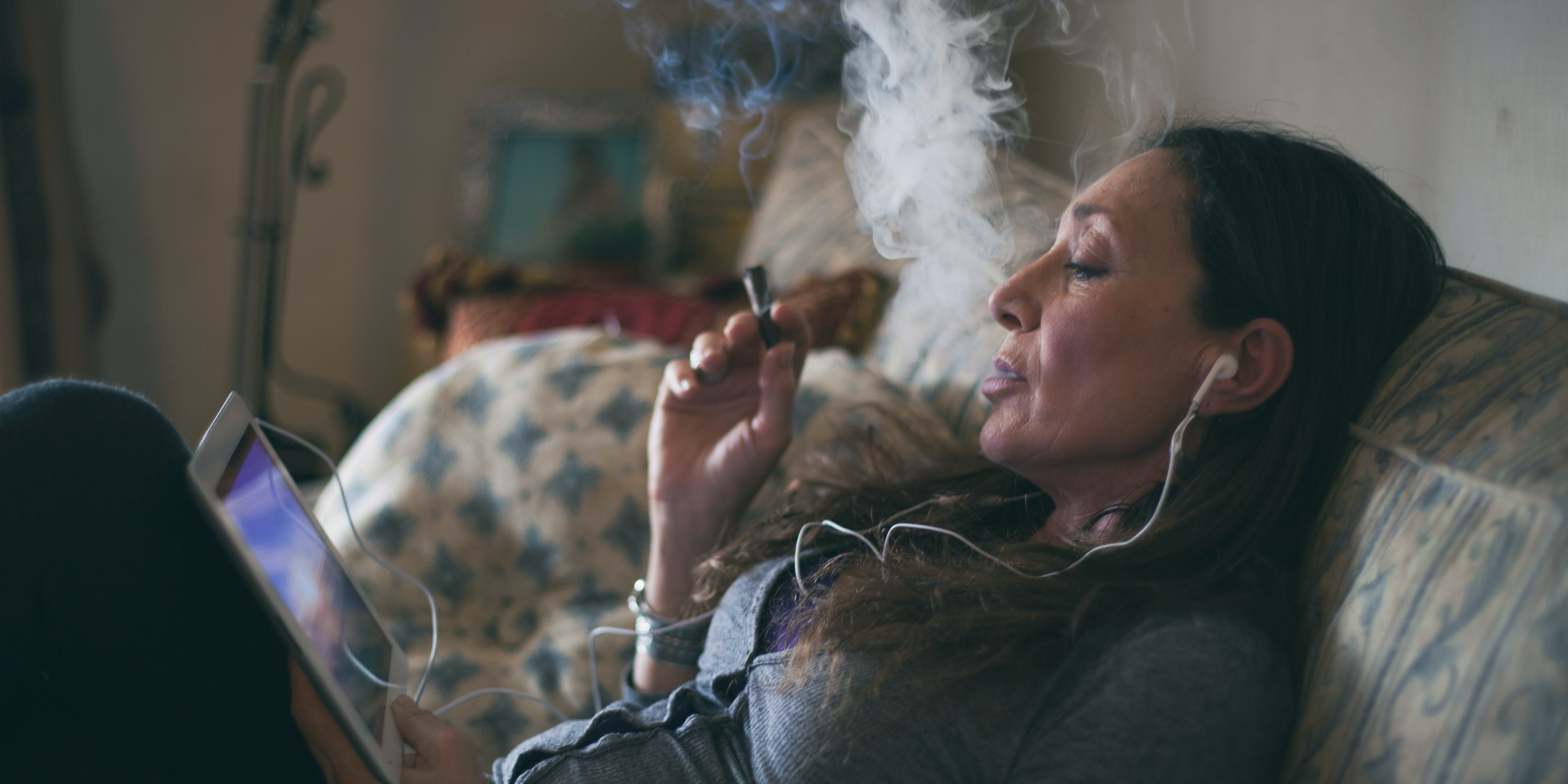 Woman relaxing on a couch, smoking a cigar and watching a video on a tablet. These are essentials for parents who smoke weed.