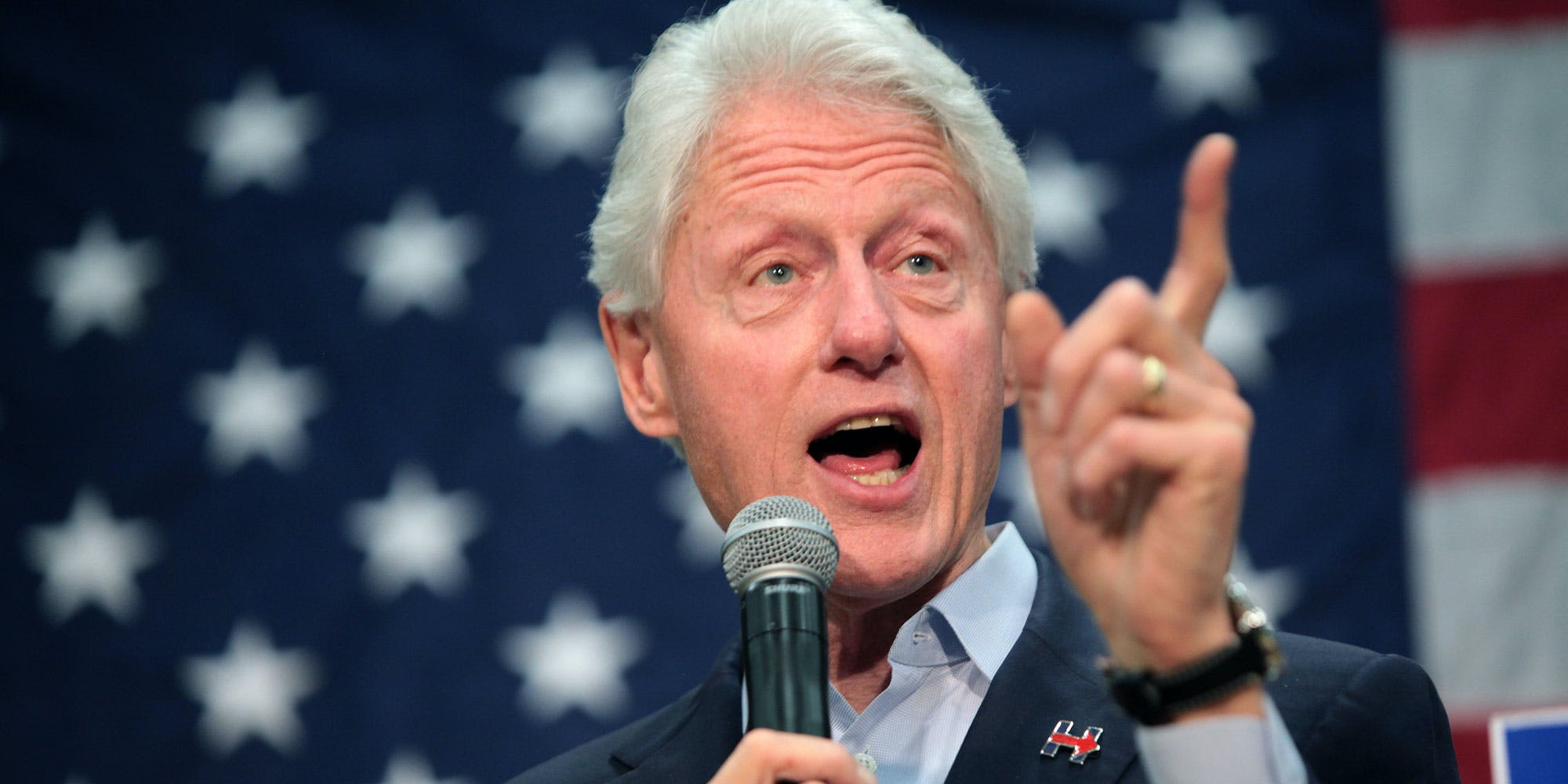 Bill Clinton pointing his finger in front of the American flag