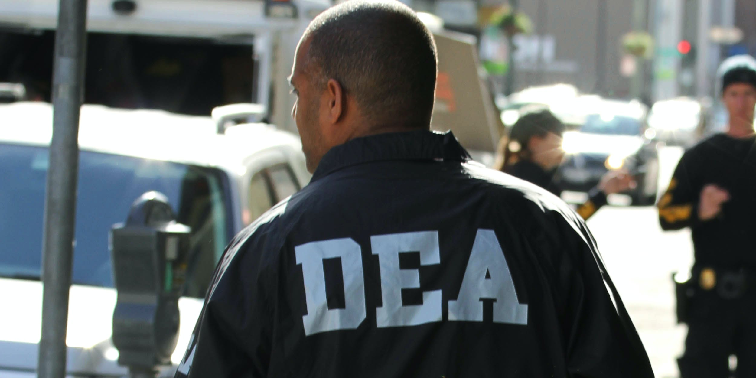 DEA agent stands with back to camera, DEA white lettering visible on jacket