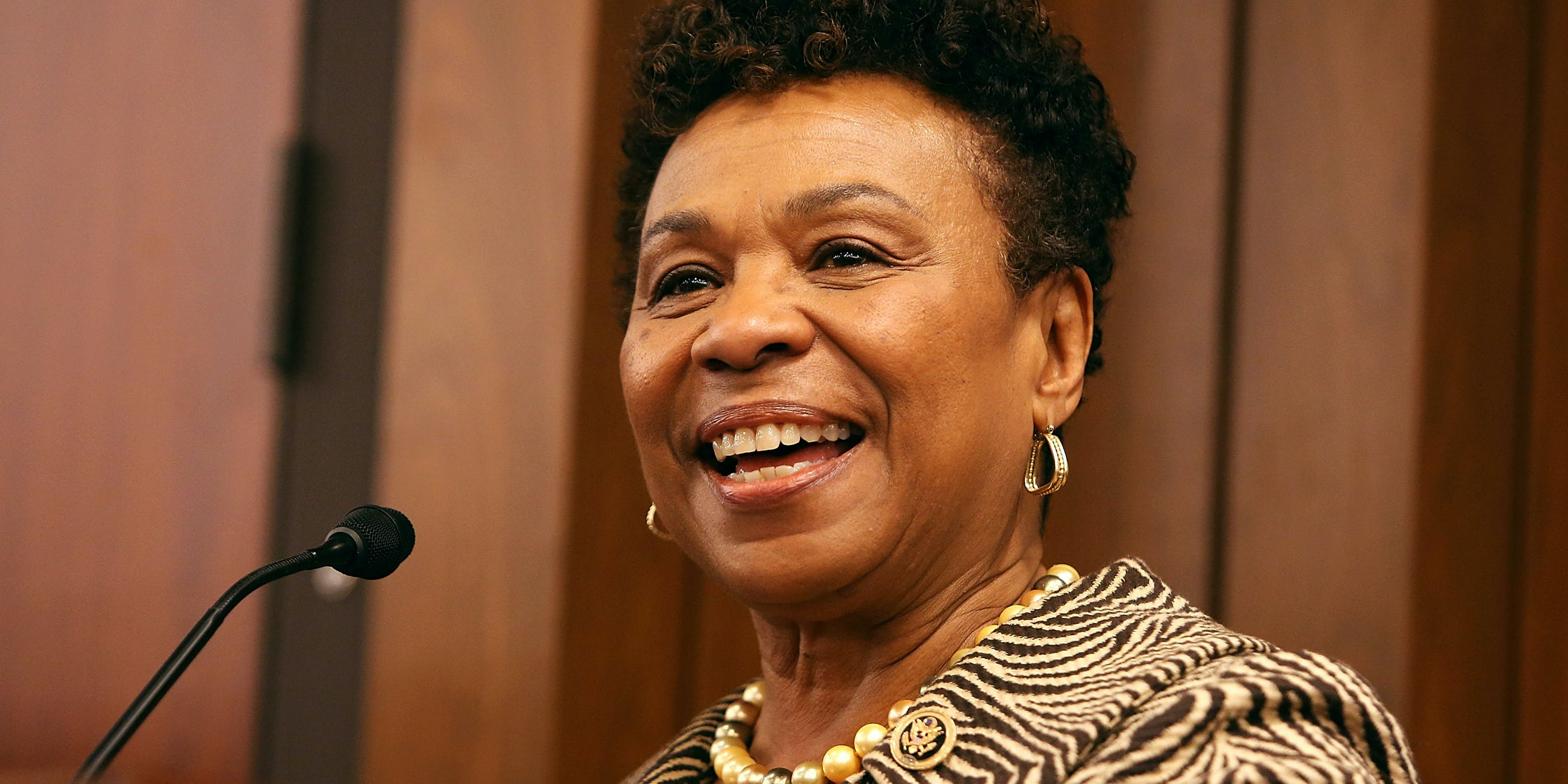 Representative Barbara Lee speaking into a microphone on stage in 2016