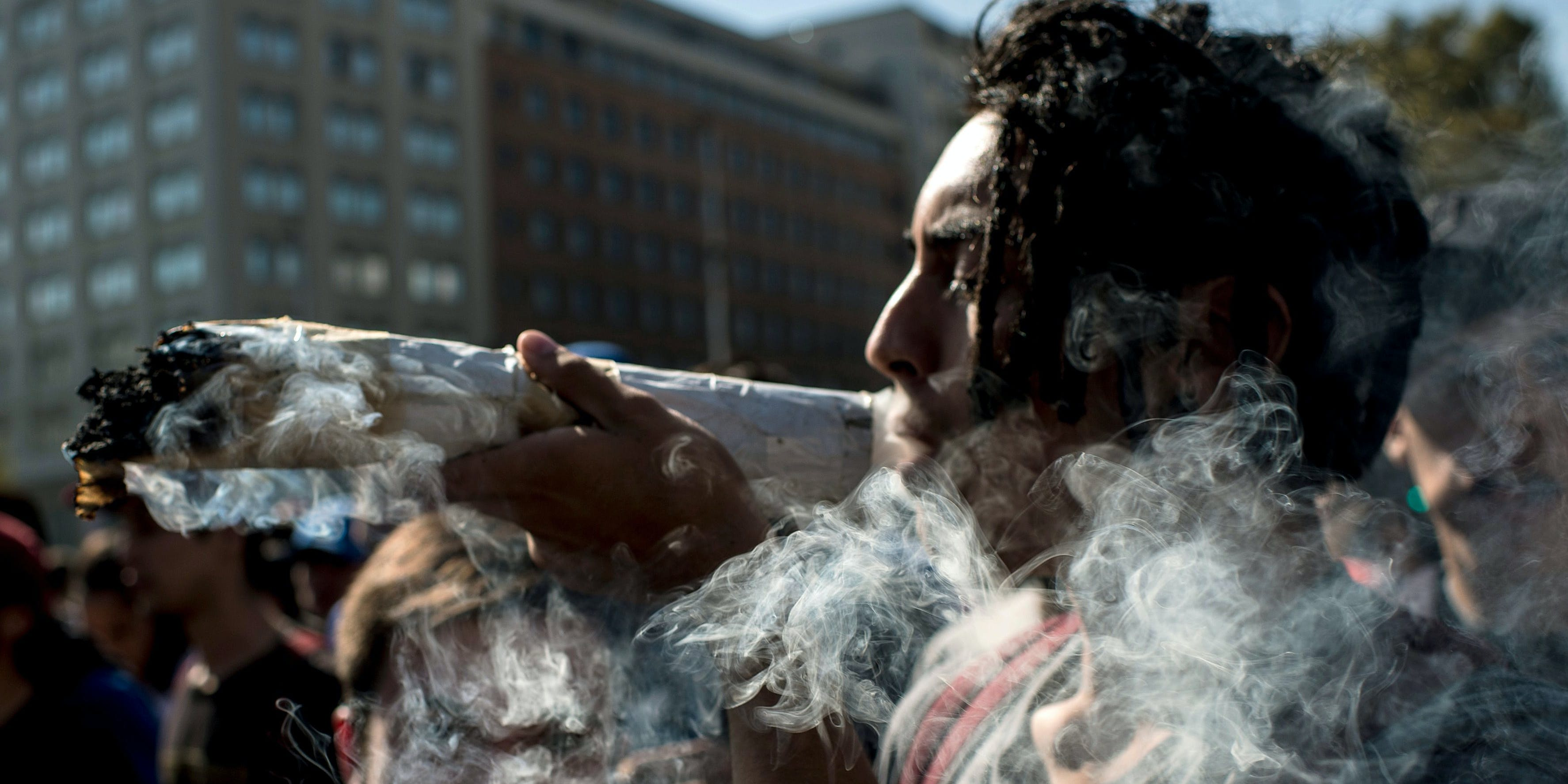 "A demonstrator with a high weed tolerance smokes a huge joint during the ""Cultivate Your Right"" rally demanding the legalization of marijuana, in Santiago, on May 05, 2018."