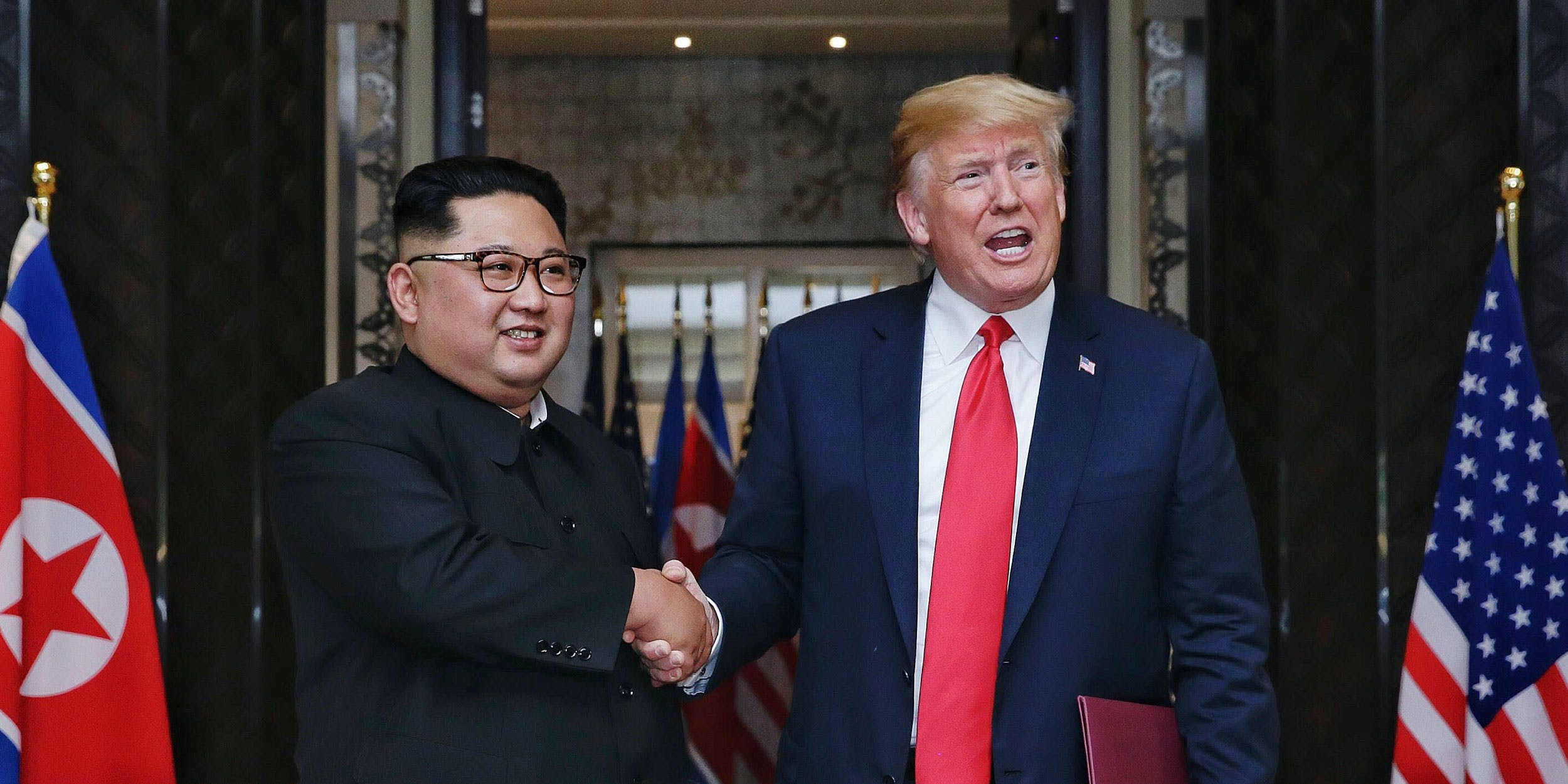 U.S. President Donald Trump (R) and North Korea's leader Kim Jong Un (L) shake their hands as they participate in a signing ceremony