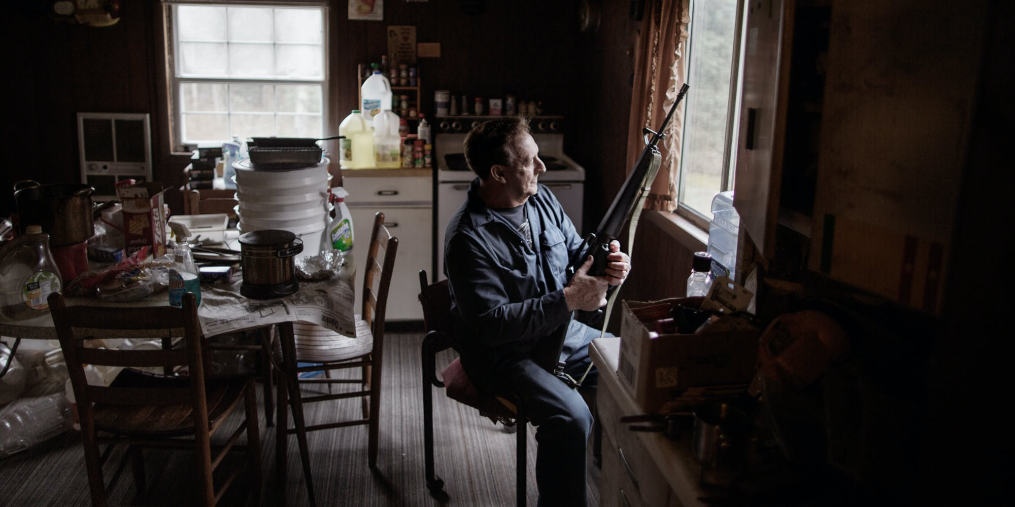 Man armed with a rifle sitting at a window of the West Virginia's Rust Belt
