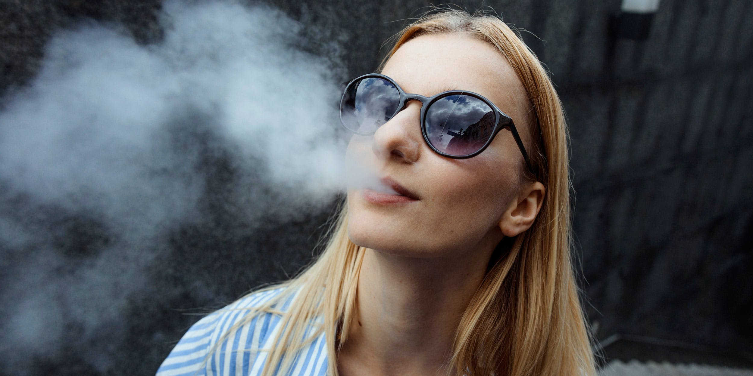 Young adult female using a convection vape