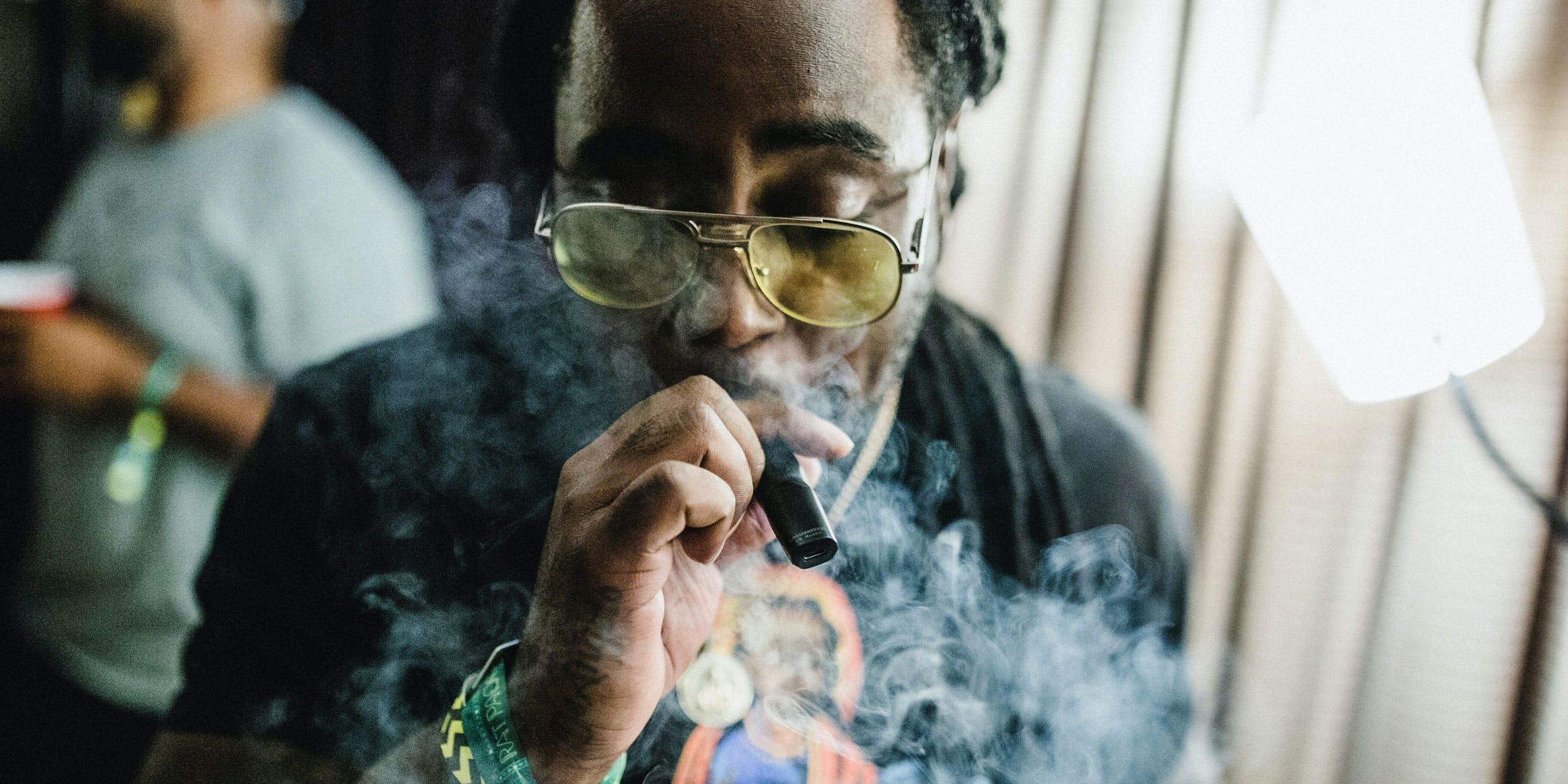 man smokes cannabis concentrates in a vape pen