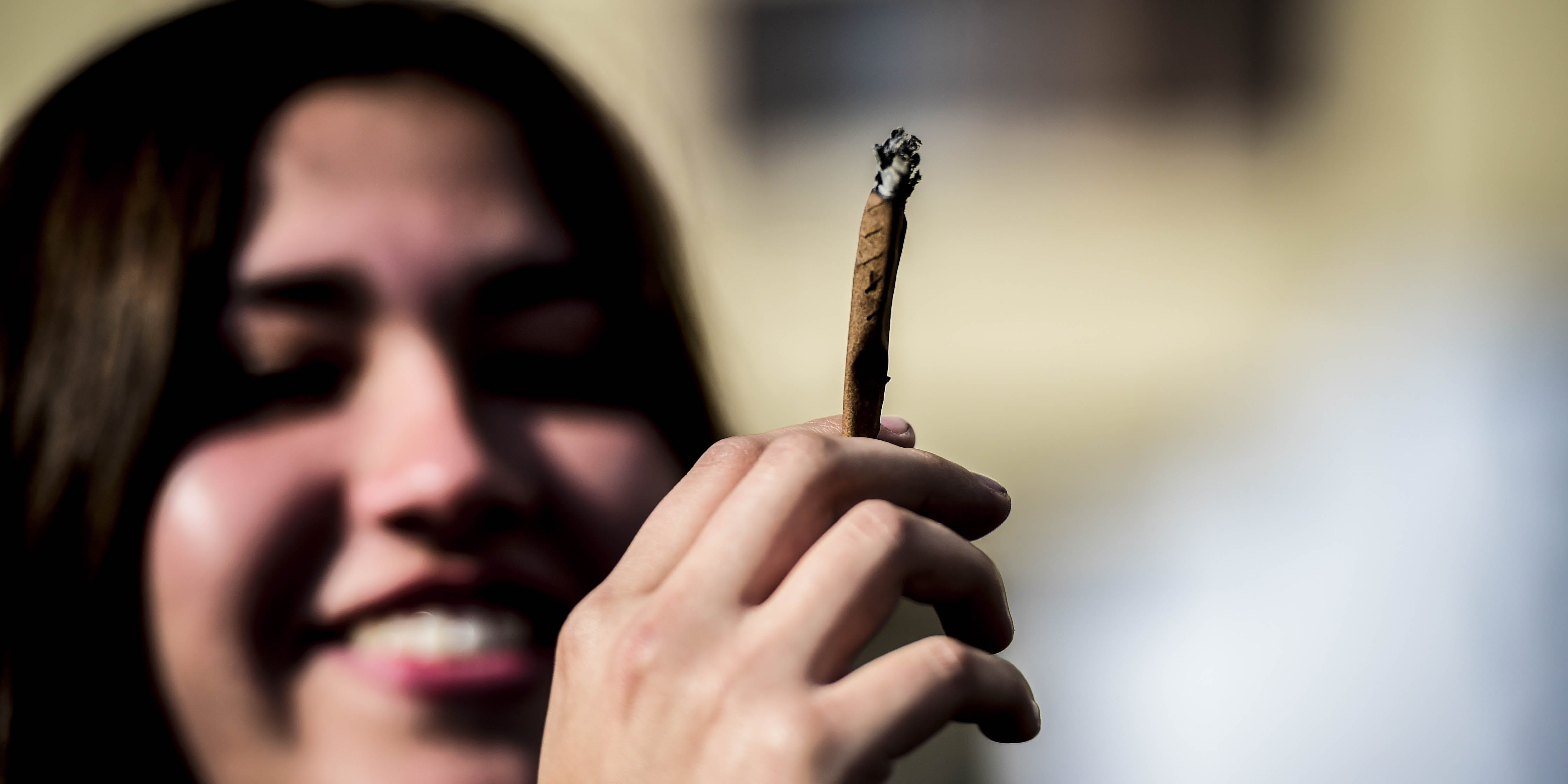 A demonstrator smokes a joint during a rally in Santiago in 2017. If legal cannabis is made too expensive, new research suggests that consumers will choose the black market over legal options.