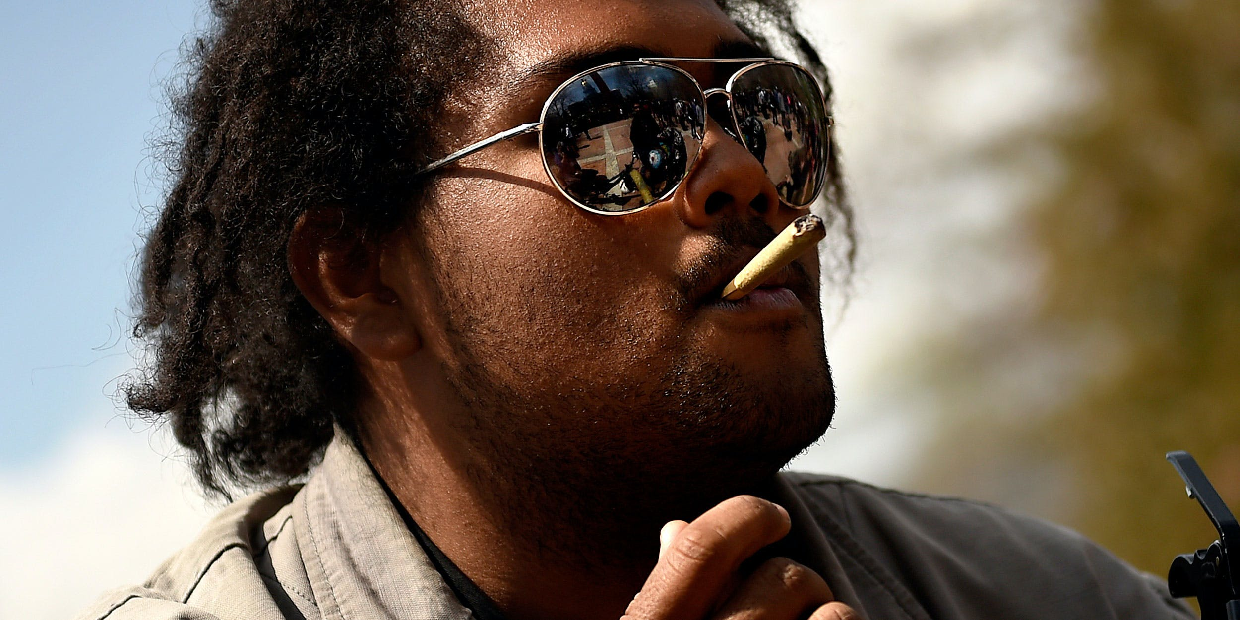 Miles of Phoenix, Arizona taking a smoke break from the guitar at the annual 420 smoke out celebration in Lincoln Park in downtown Denver on April 20, 2015. Photo By Joe Amon/The Denver Post via Getty Images)