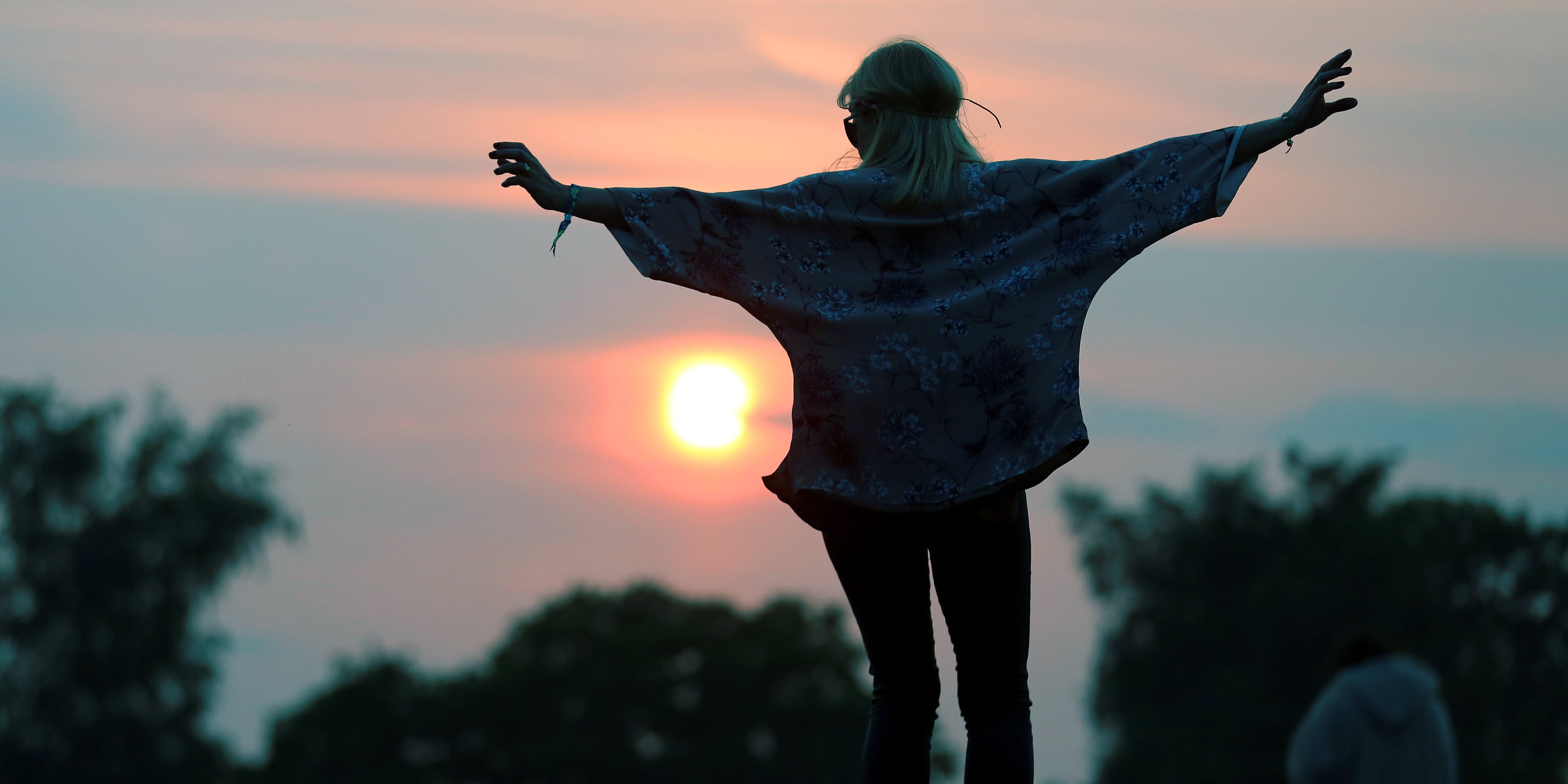 GLASTONBURY, ENGLAND - JUNE 26: A woman stands on a rock at the stone circle as people gather for sunset at the Glastonbury Festival of Contemporary Performing Arts site at Worthy Farm, Pilton on June 26, 2013 near Glastonbury, England. Northern Nights in the Emerald Triangle just announced major discounts for attendees who buy the local weed