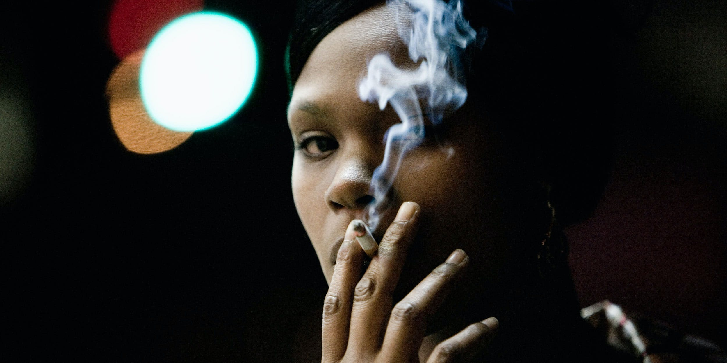 Woman smoking a cigarette. Imperial Brands is investing in the cannabis industry