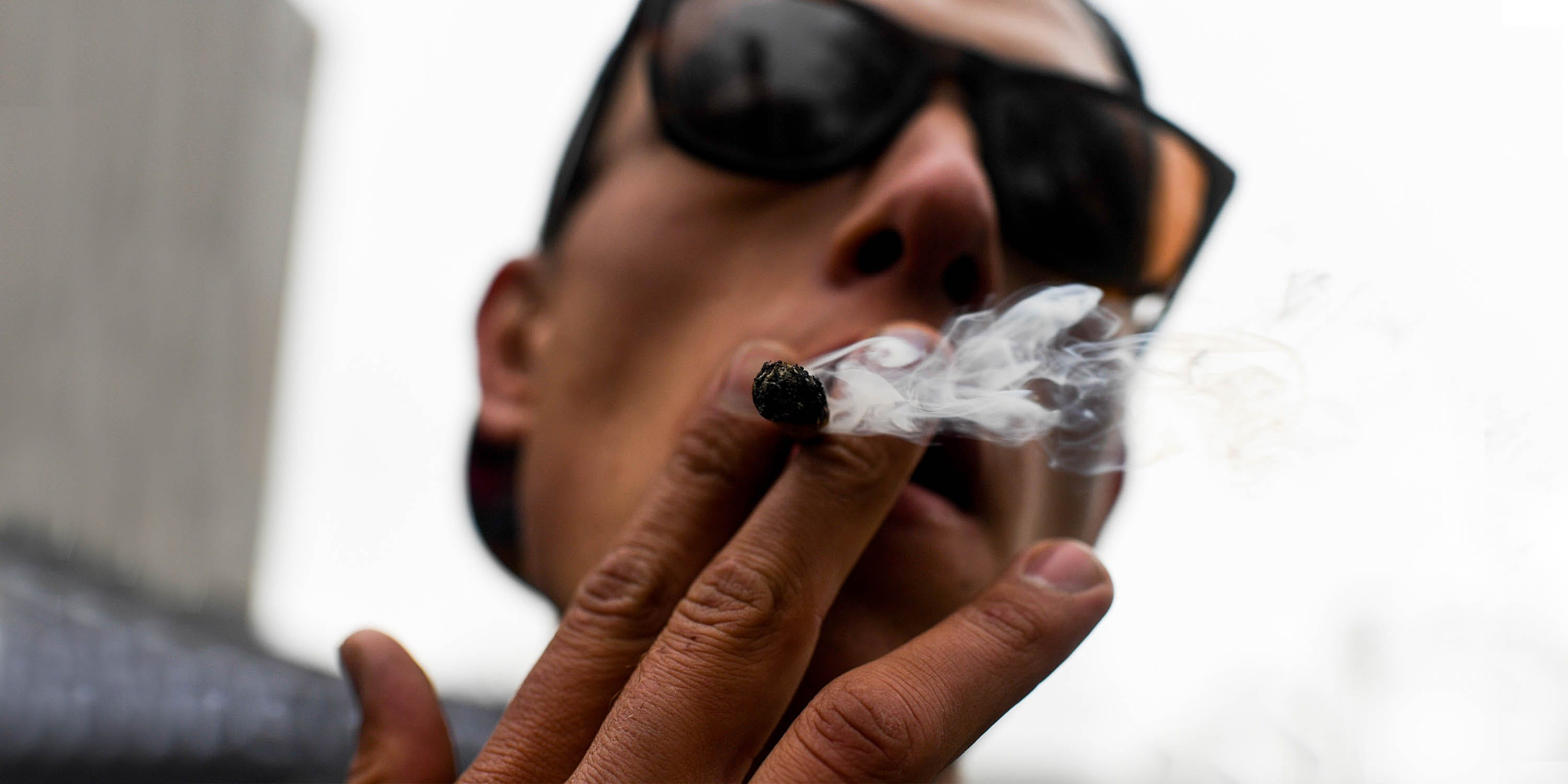 A man smokes a blunt while wearing glasses. Statistics show that cannabis use disorder is a real thing, and numbers are soaring.