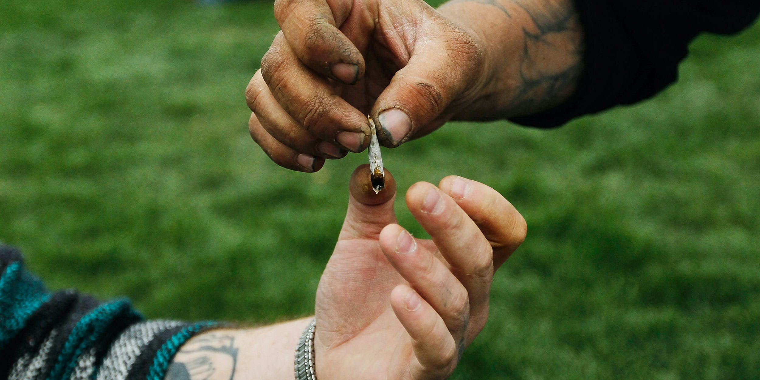 "Men pass a marijuana cigarette to each other during a pro-marijuana rally at Civic Center Park with the Colorado State Capitol Building in the background on April 20, 2010 in Denver, Colorado. The DEA just updated its list of drug slang, which includes terms for weed like ""pink panther."""