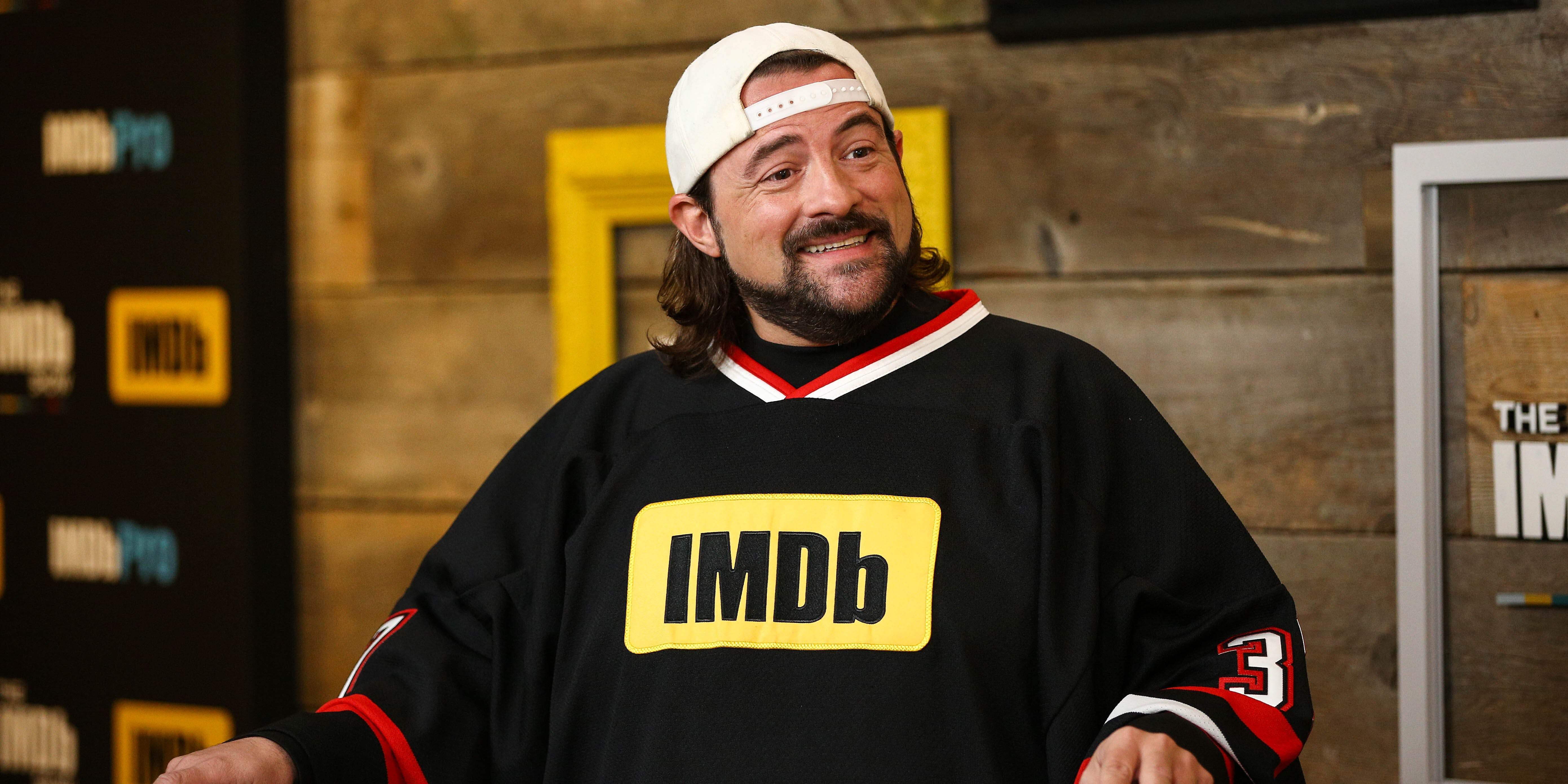 Kevin Smith wears an IMDb shirt during an interview. He is crowdfunding for his next comedy series 'Hollyweed'