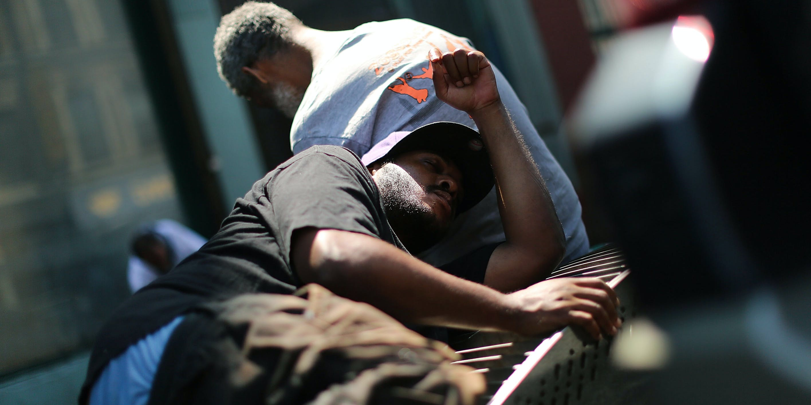 """NEW YORK, NY - AUGUST 05: Men who are high on K2 or """"Spice,"""" a synthetic cannabis drug, sleep along a street in East Harlem on August 5, 2015 in New York City. (Photo by Spencer Platt/Getty Images)"""