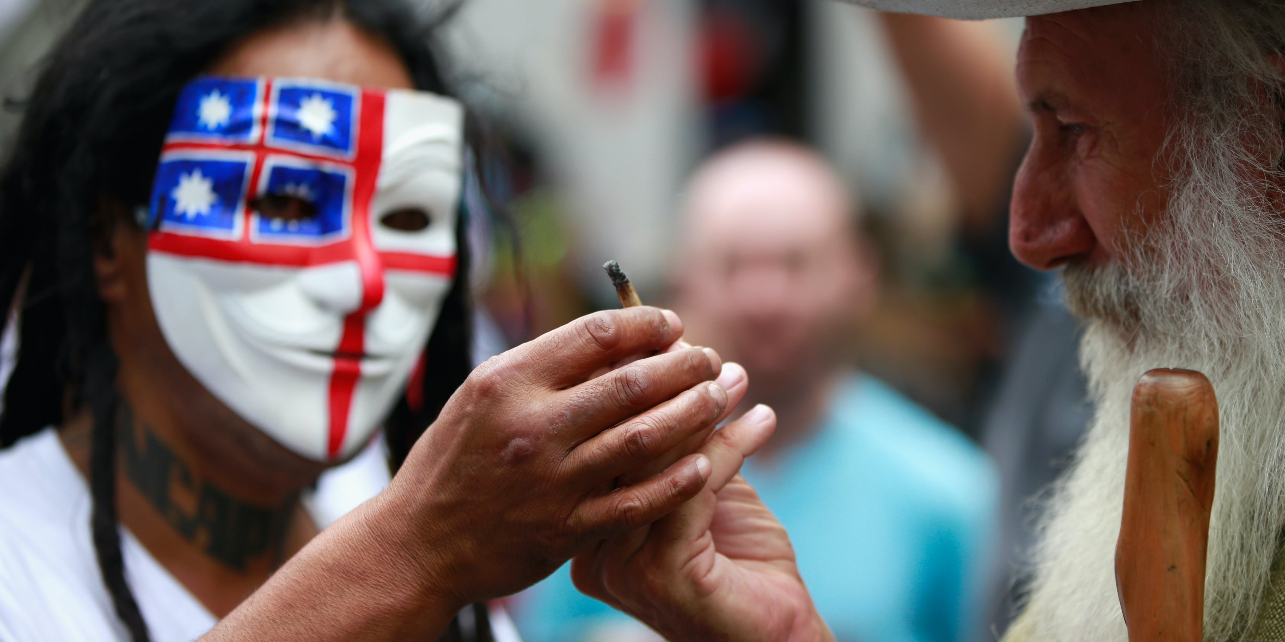 Cannabis protestors smoke outside the Sky City Convention in New Zealand. A man smokes a joint. A recent survey finds that New Zealand is overwhelmingly in support of cannabis reform.