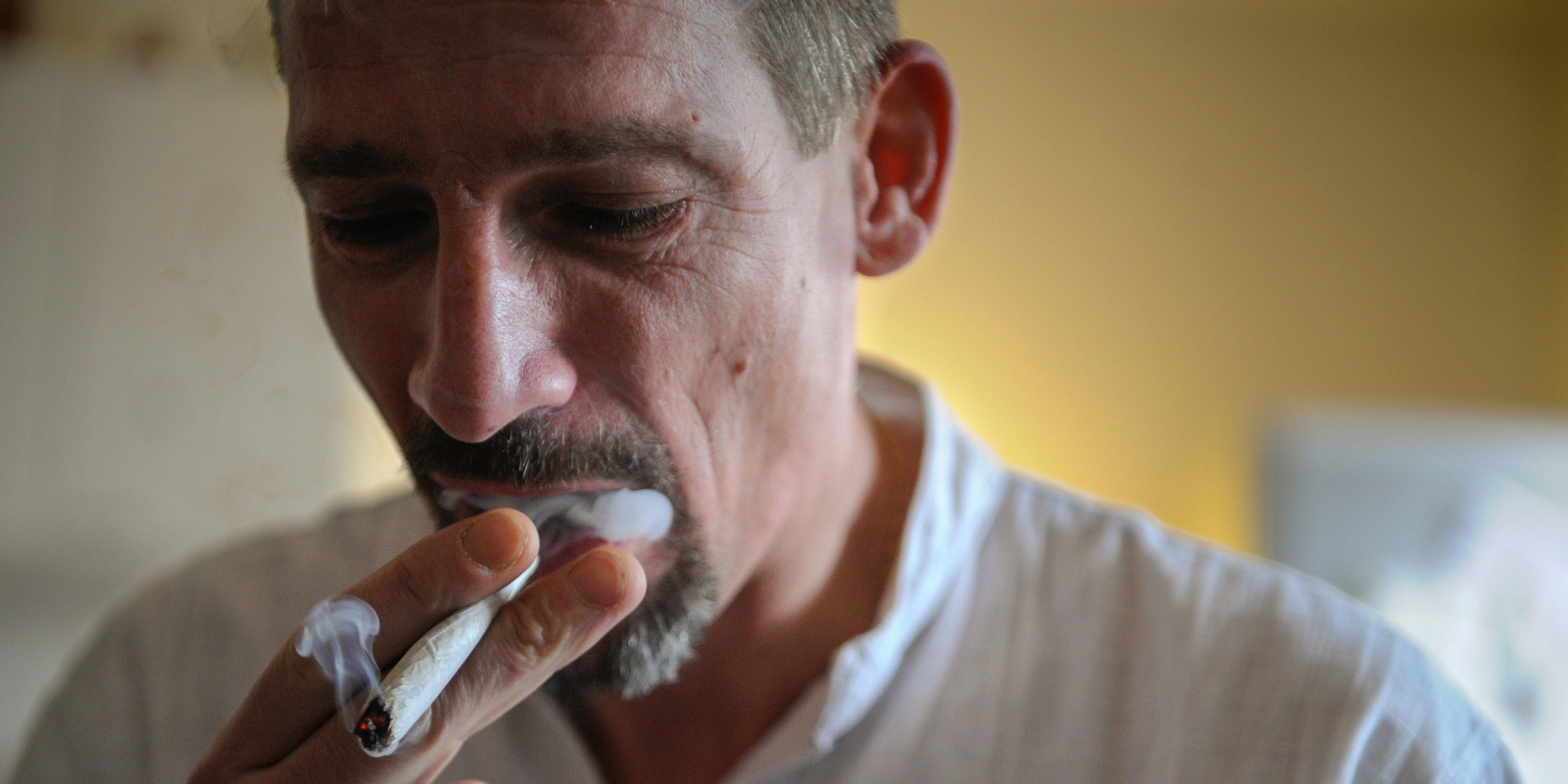 Dominique Loumachi, suffering from Dermatomyositis (Myopathy), smokes a cigarette that looks like a cannabis cigarette in order not to be charged for promoting consumption of narcotic substances while posing on February 28, 2013 in Belfort, Eastern France. Rhode Island dispensaries recently announced that they would recognize out-of-state medical marijuana licenses.