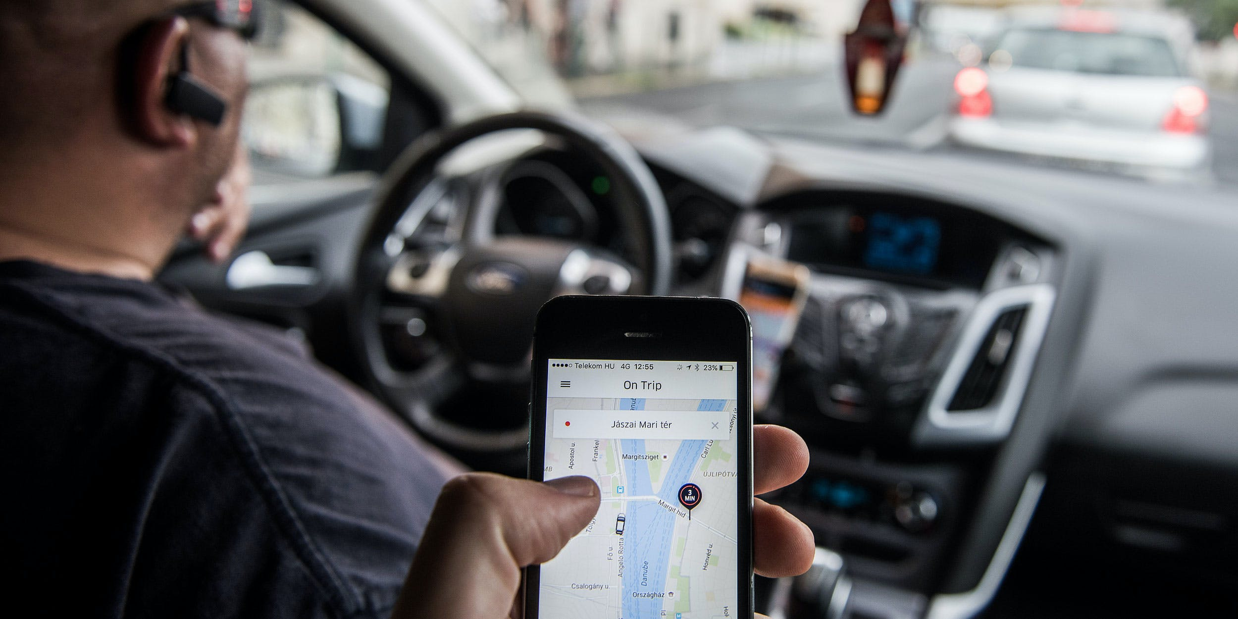 A passenger holds an iPhone displaying the Uber Technologies Inc. car service taxi application.