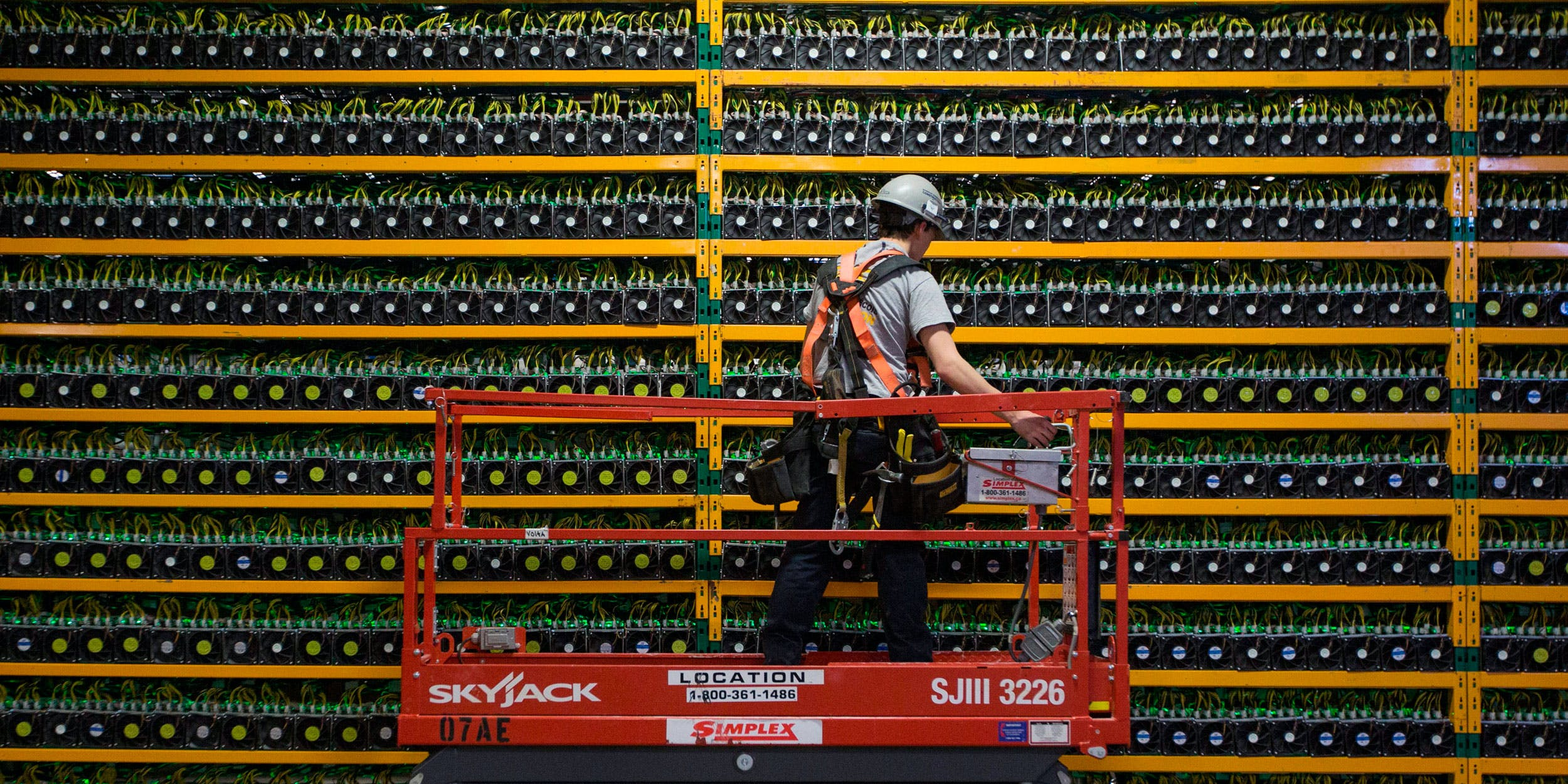 A technician inspects the backside of Bitcoin mining at Bitfarms in Saint Hyacinthe, Quebec on March 19, 2018. Bitcoin is a cryptocurrency and worldwide payment system. It is the first decentralized digital currency, as the system works based on the Blockchain technology without a central bank or single administrator. (Photo by Lars Hagberg /AFP/Getty Images)